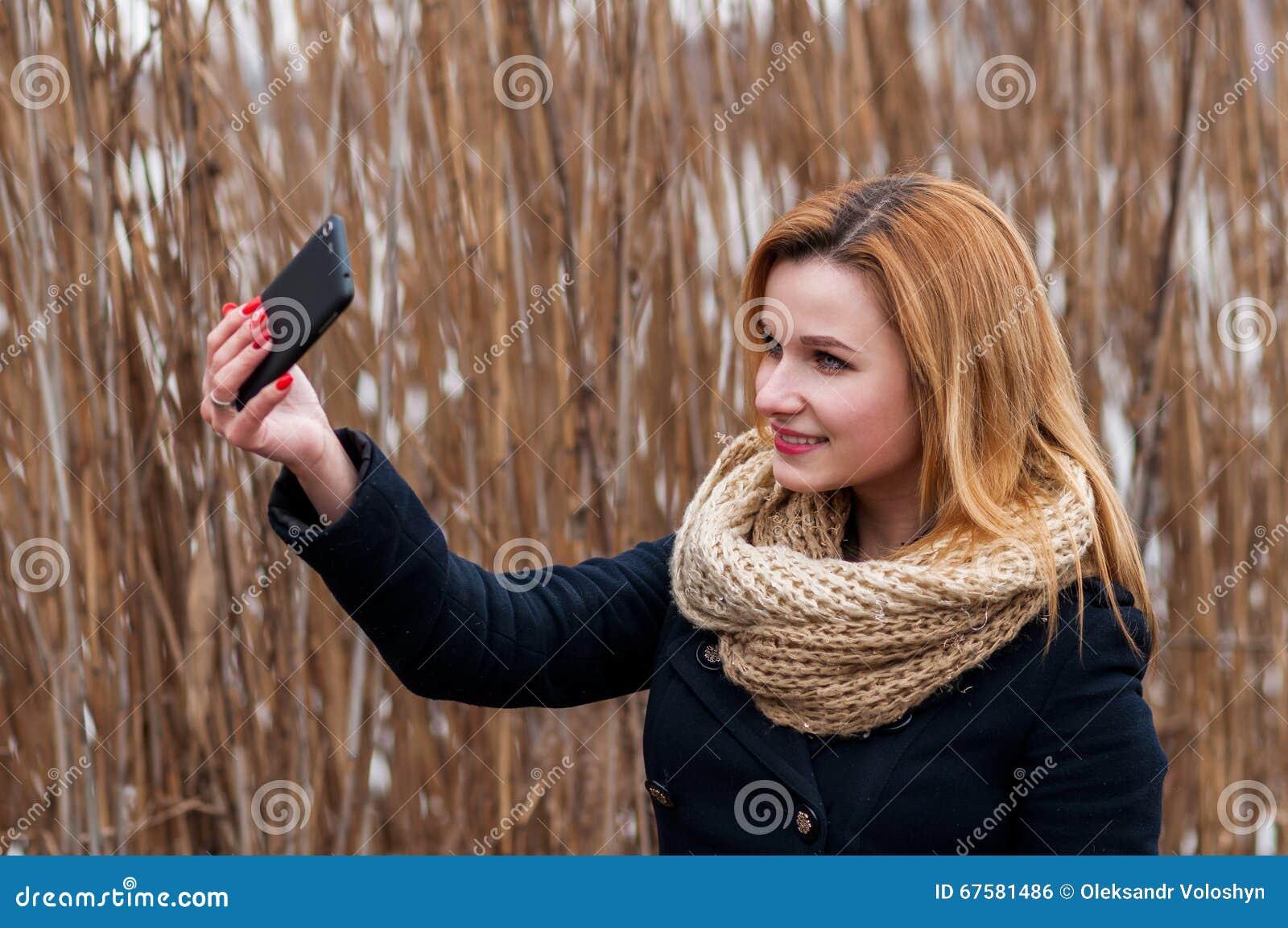 拍与巧妙的电话的美丽的少妇特写镜头一张selfie照片户外