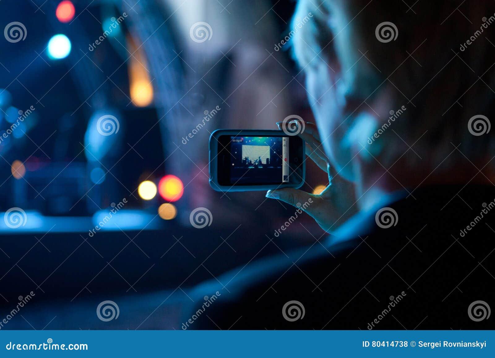 拍与手机的女商人照片在音乐会