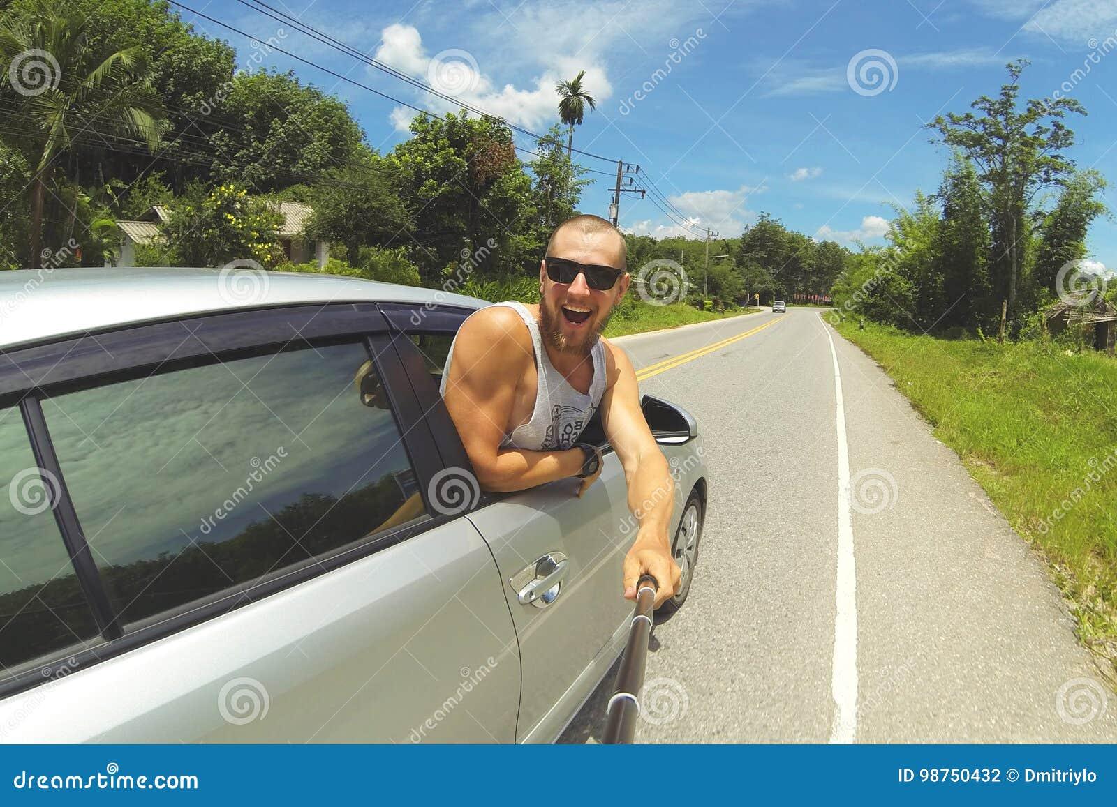 拍与智能手机的年轻愉快的人Selfie照片在Monopod棍子 做旅行照片的行家由车窗
