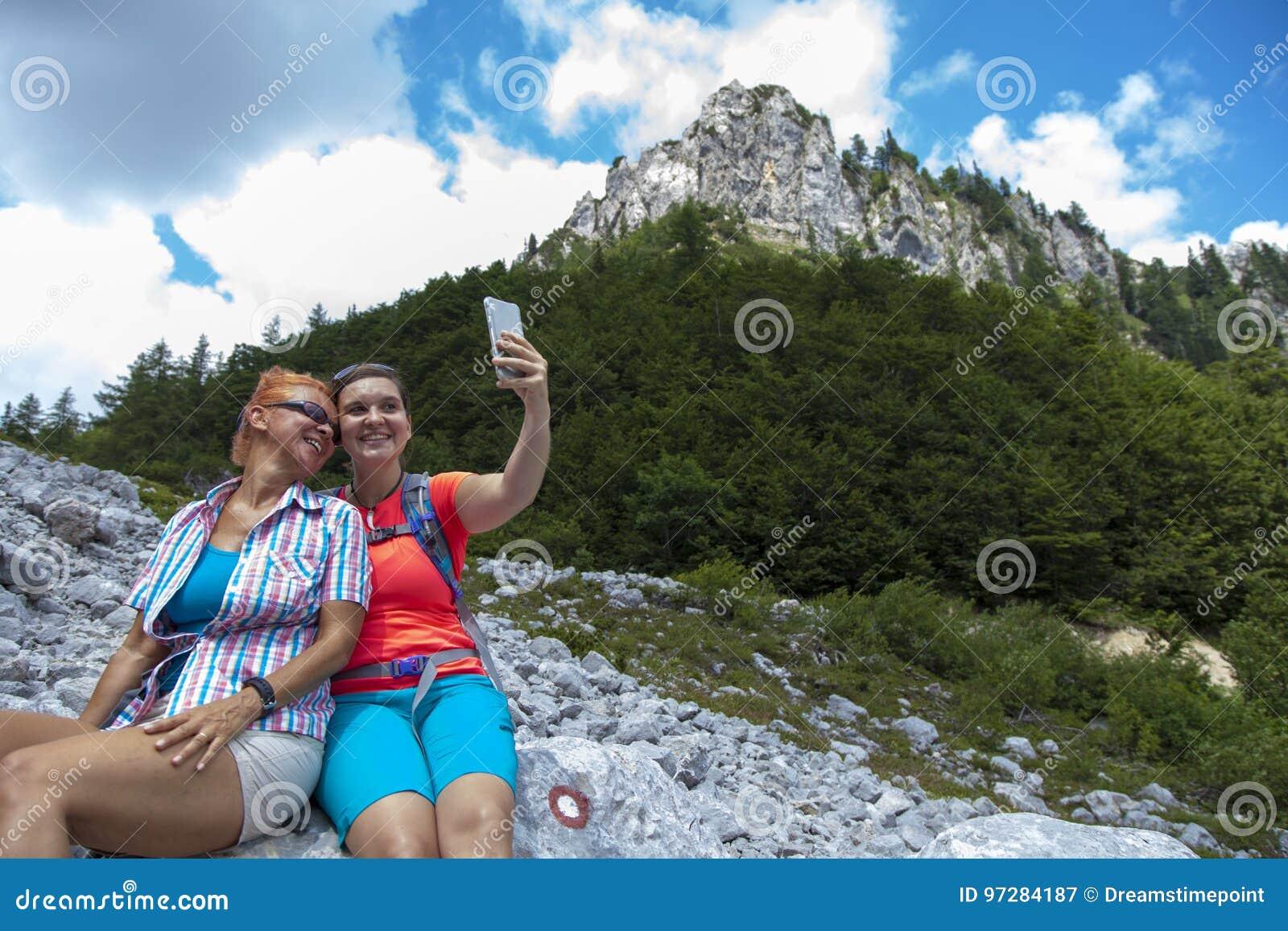 拍摄在山峰的两名相当女性妇女一selfie