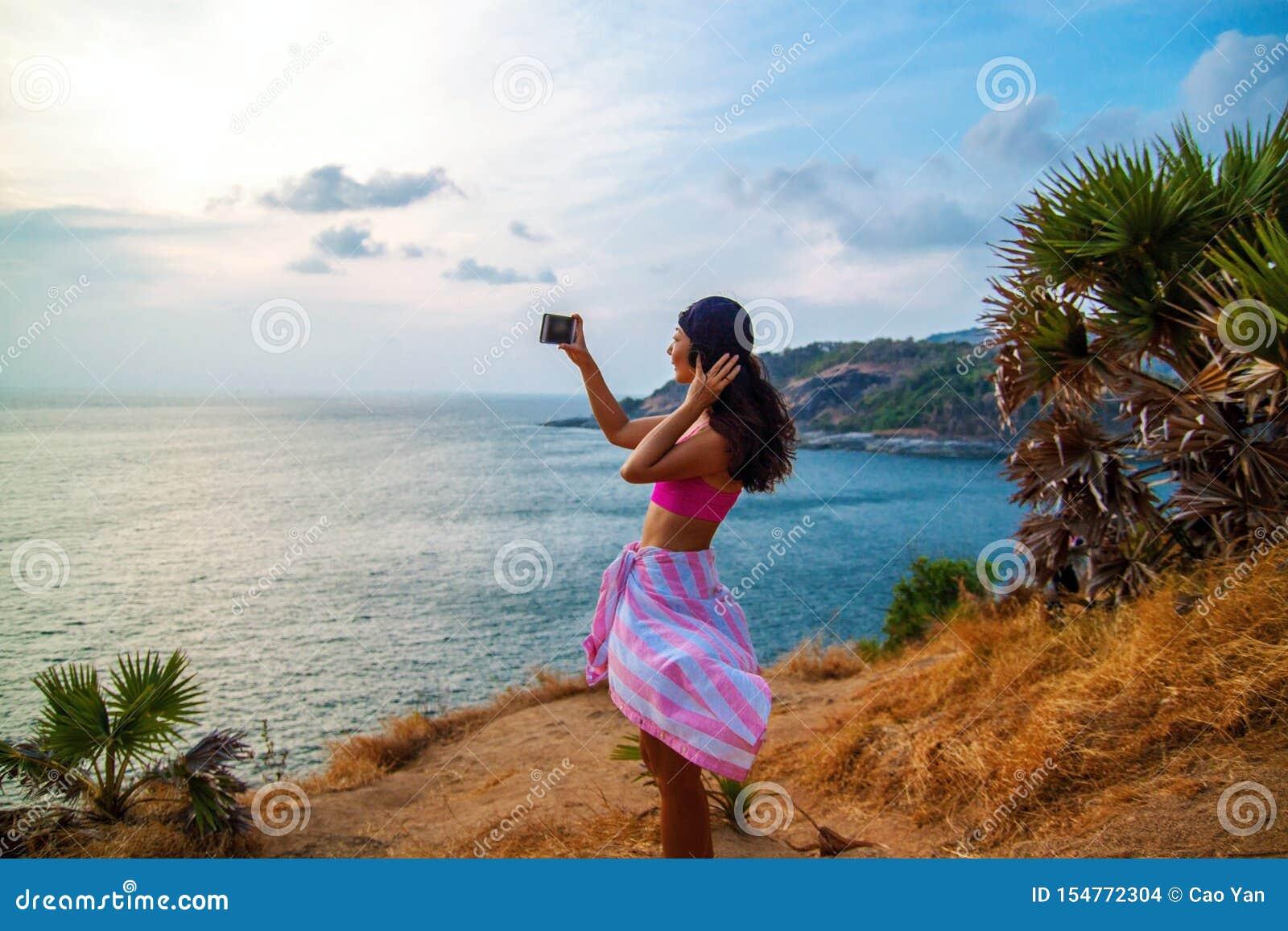 拍摄有智能手机的妇女背面图海,当站立在船反对天空蔚蓝时
