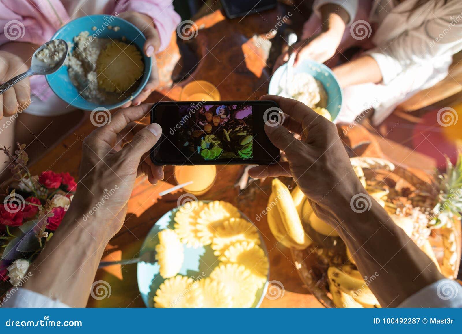 拍早餐桌的照片男性手油罐顶部角钢视图用新鲜水果和燕麦粥粥