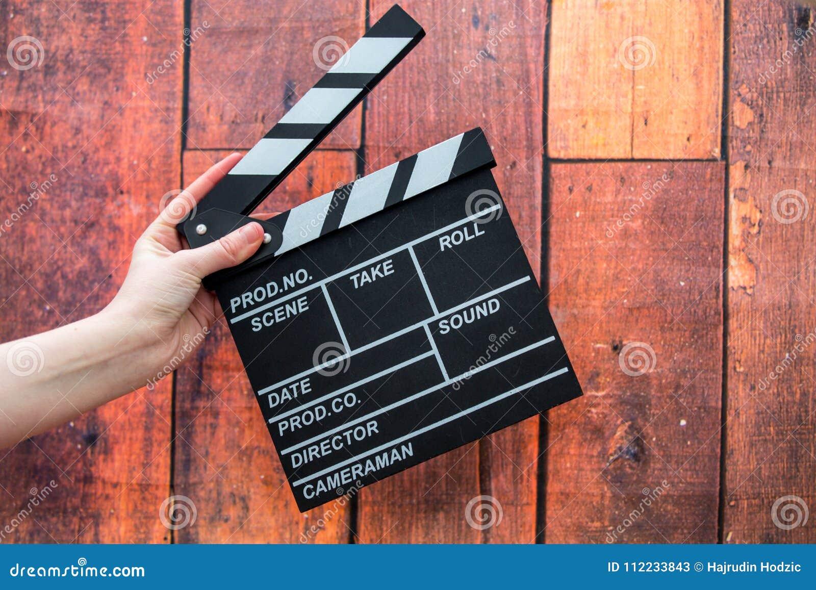 拍板板材、妇女` s手和影片拍板在一木backg
