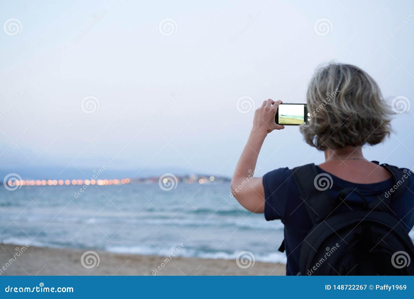拍海的照片的智能手机的妇女在日落