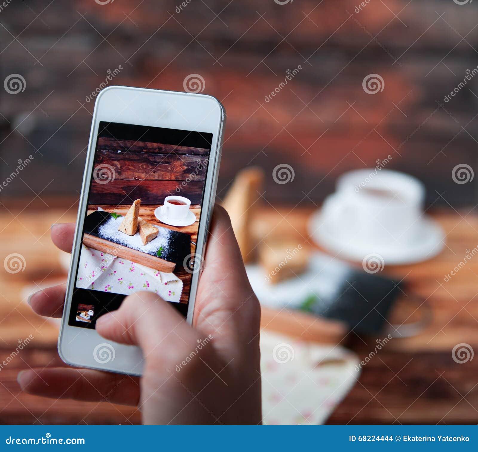 拍点心的照片与智能手机的妇女