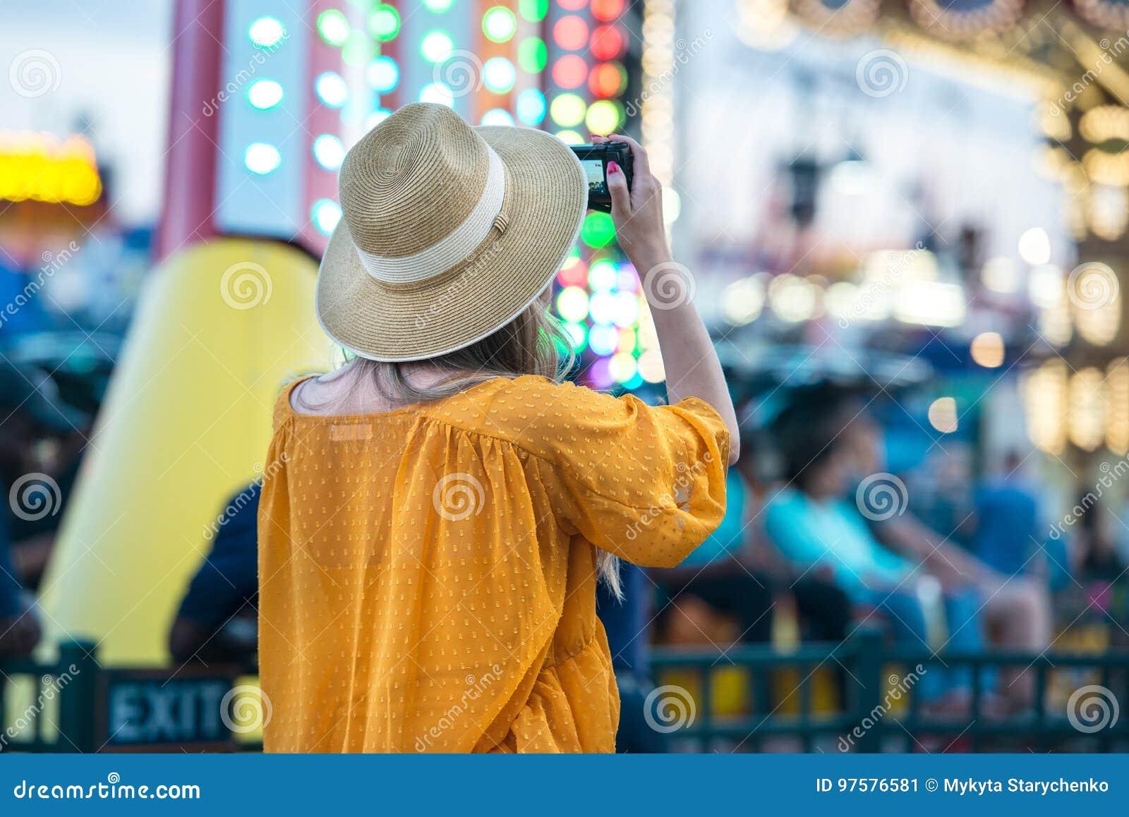 拍照片的妇女在游乐园在她的旅行期间暑假