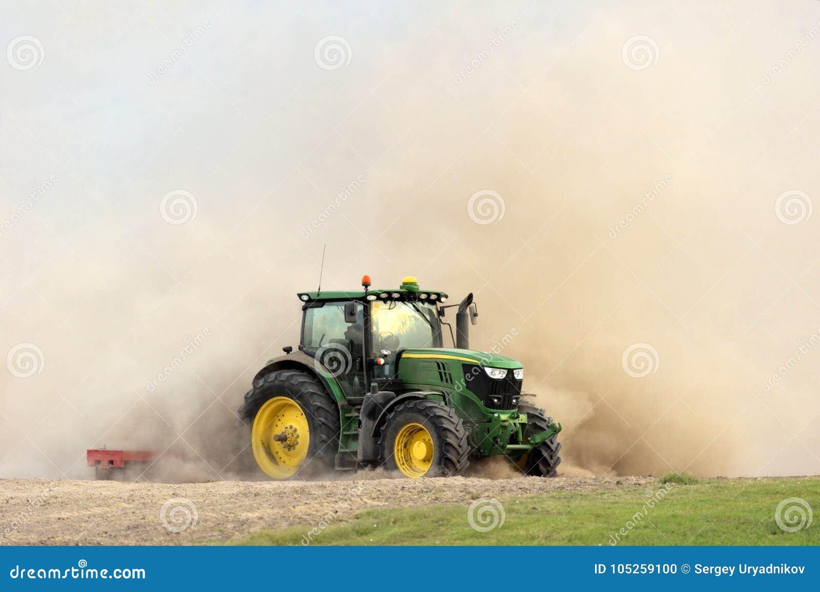 拖拉机耙松在巨大的尘云的领域