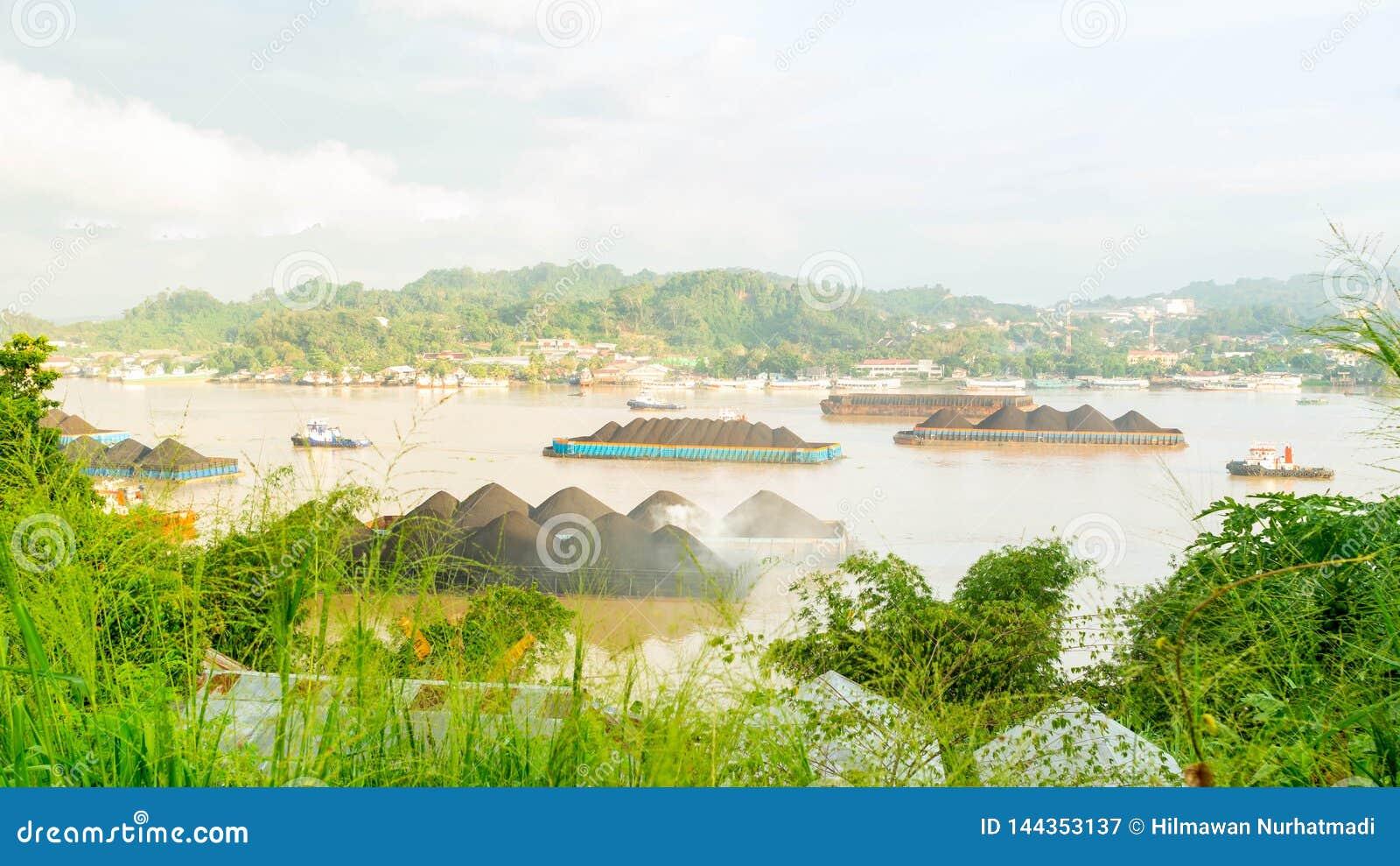 拖轮交通美丽的景色拉扯煤炭的驳船在马哈坎河,沙马林达,印度尼西亚