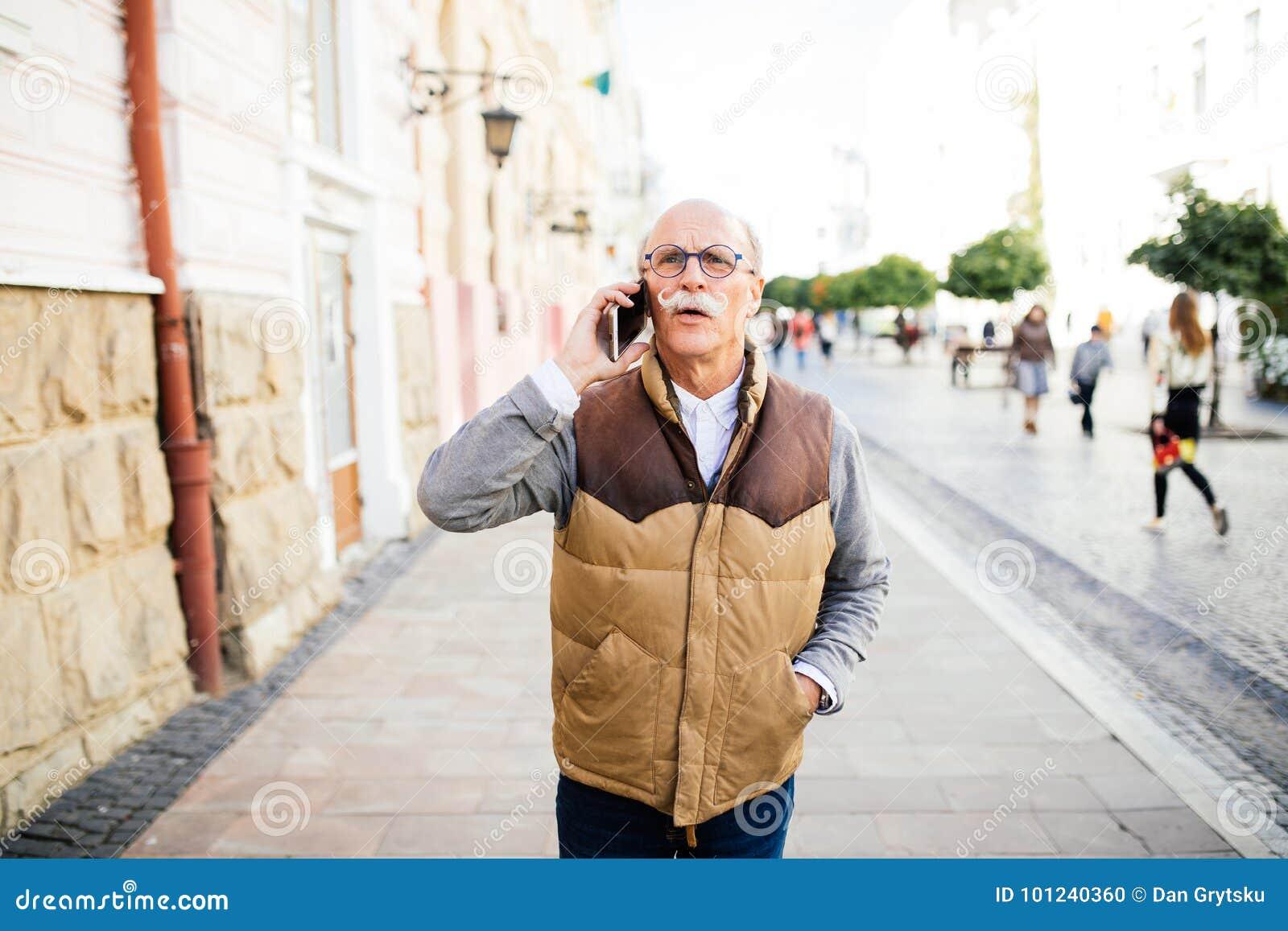 拜访智能手机的愉快的老人在城市