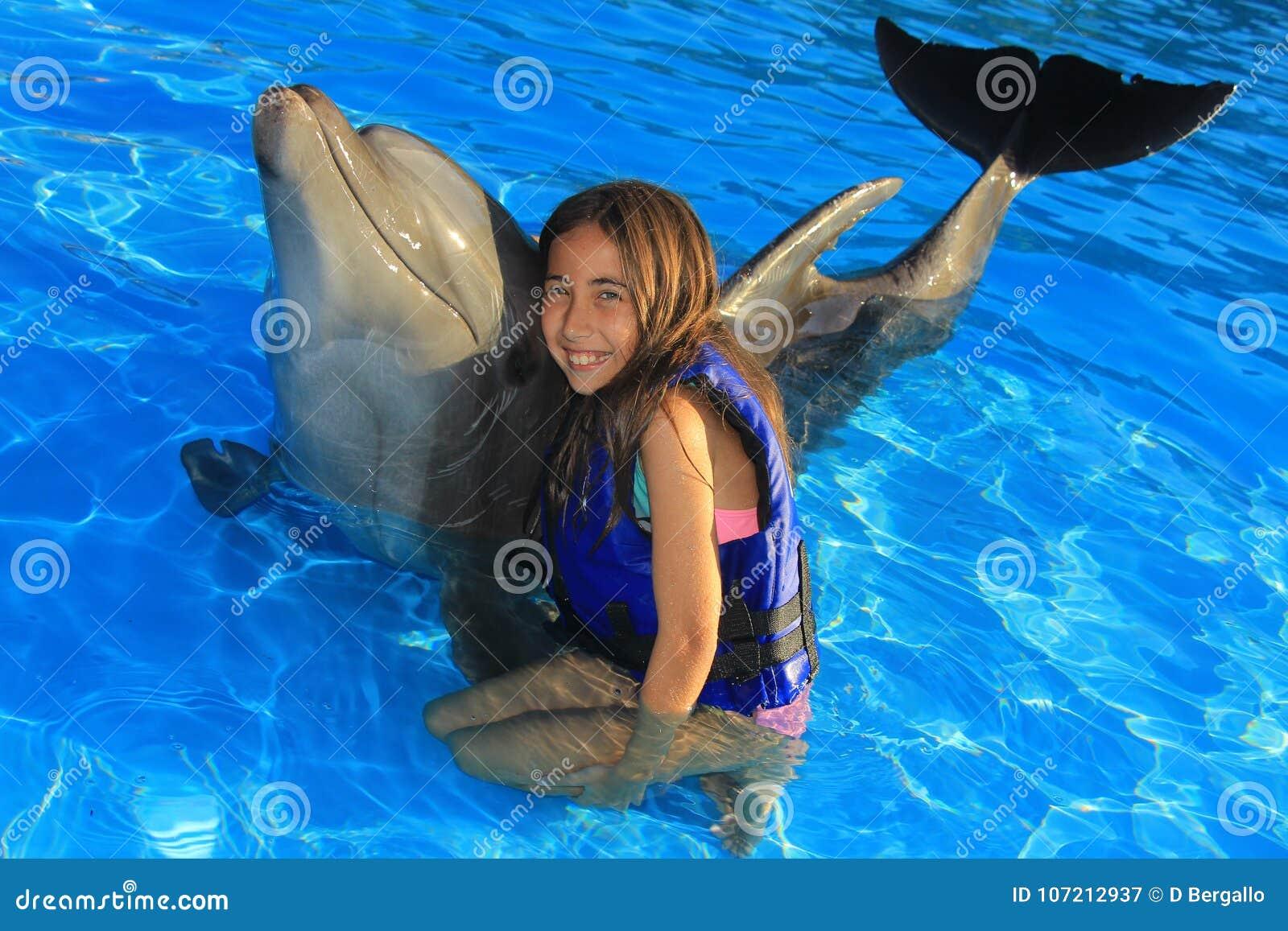 拥抱一个华美的海豚鸭脚板微笑的面孔愉快的孩子的小女孩孩子游泳瓶鼻子海豚
