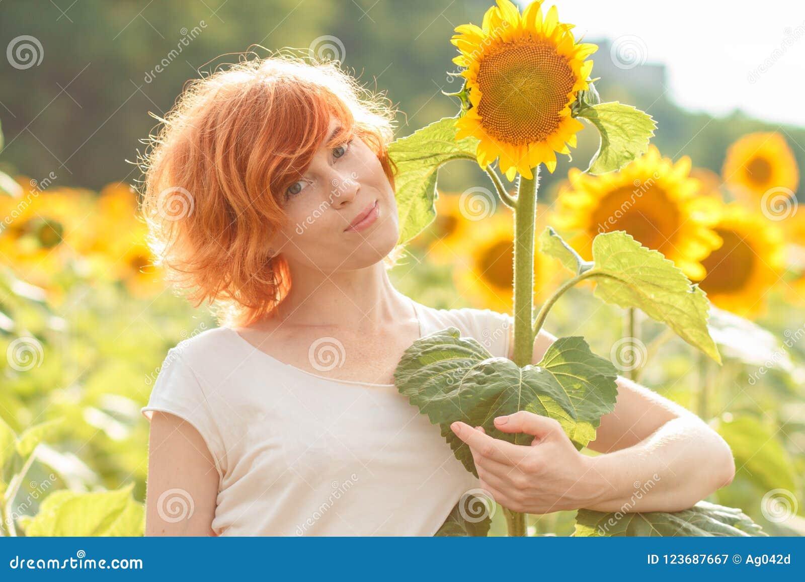 拥抱一个高向日葵的红发女孩在日落,年轻redhea