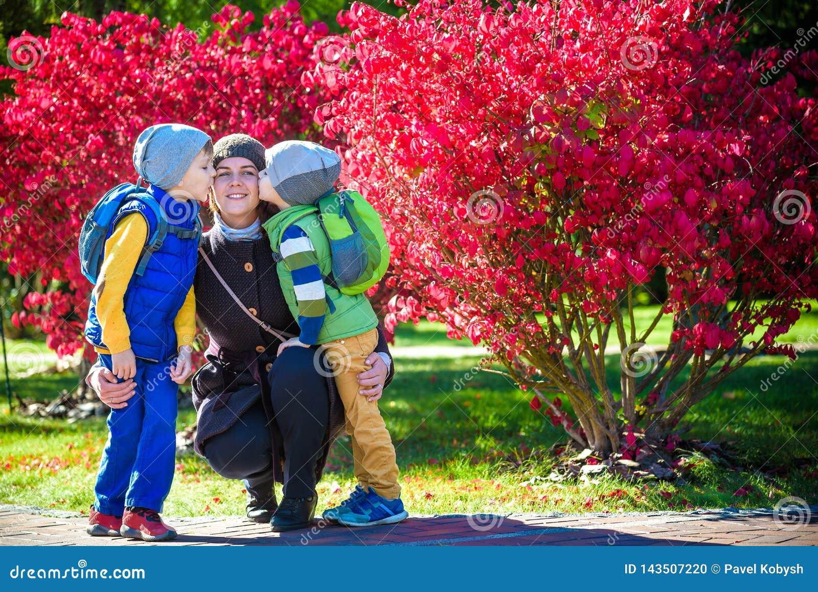 拥抱两个小孩,幸福家庭,有两室外的儿子的逗人喜爱的深色的女性特写镜头画象的年轻母亲的图片