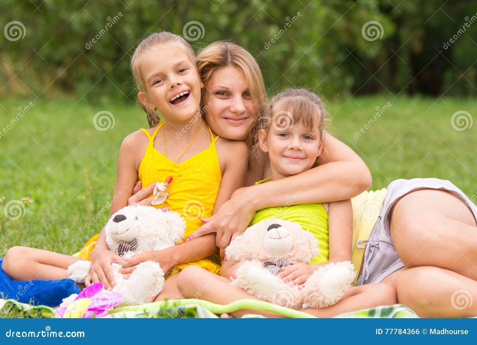 拥抱两女儿,五和七年的野餐的年轻母亲