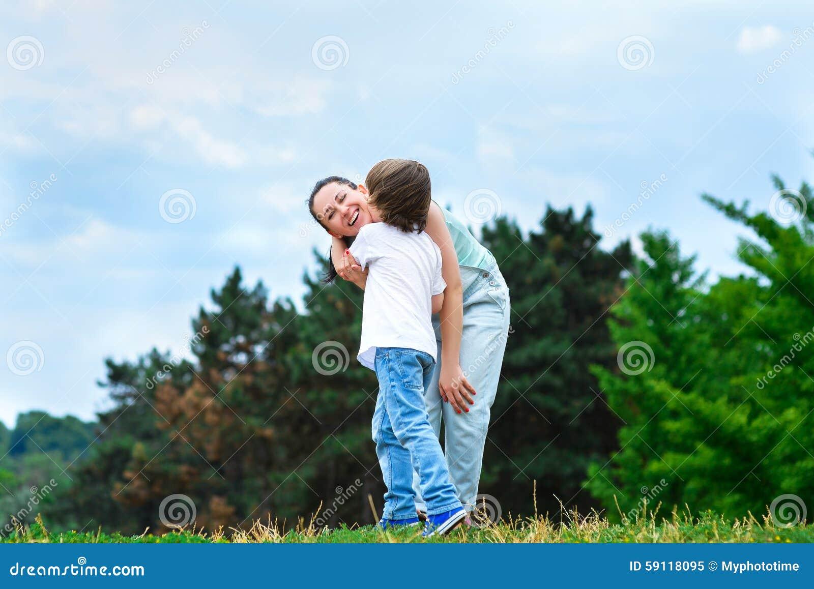 拥抱和亲吻他愉快的母亲的爱恋的儿子