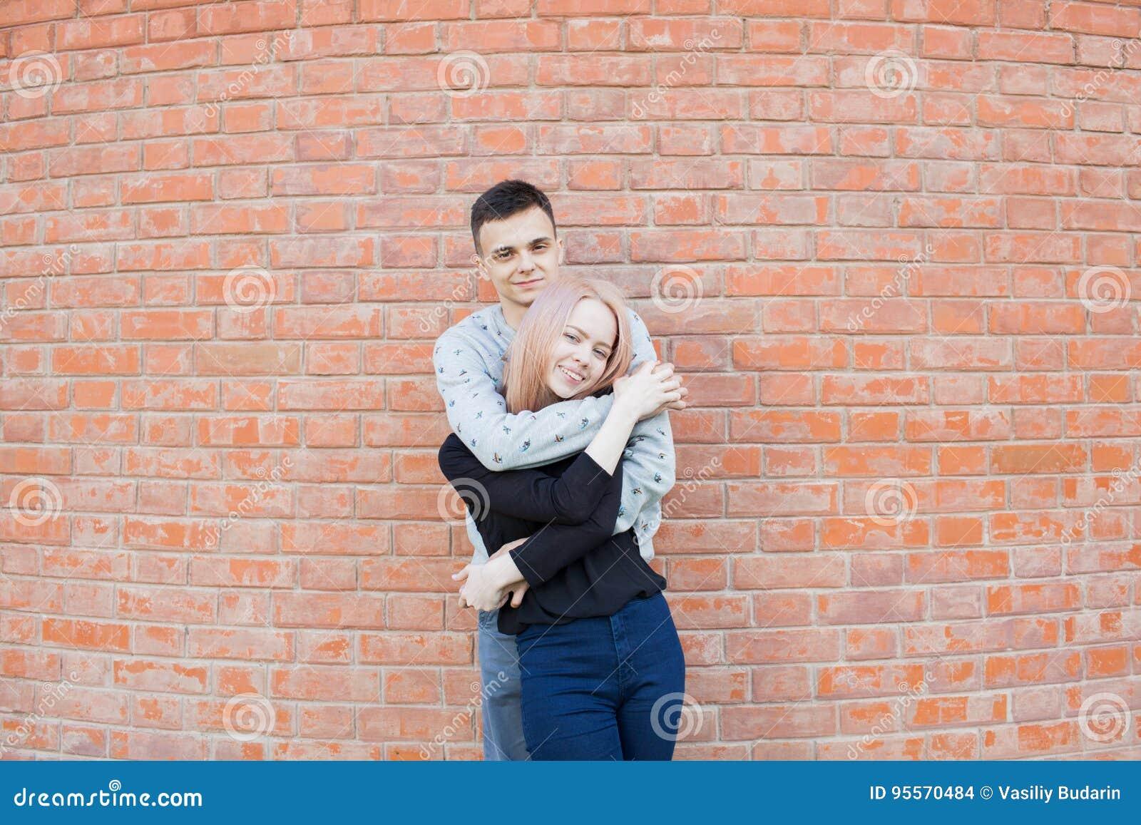 拥抱和微笑在红砖墙壁背景的愉快的年轻夫妇  有蓝眼睛的白肤金发的女孩和阿拉伯appea的一个年轻人