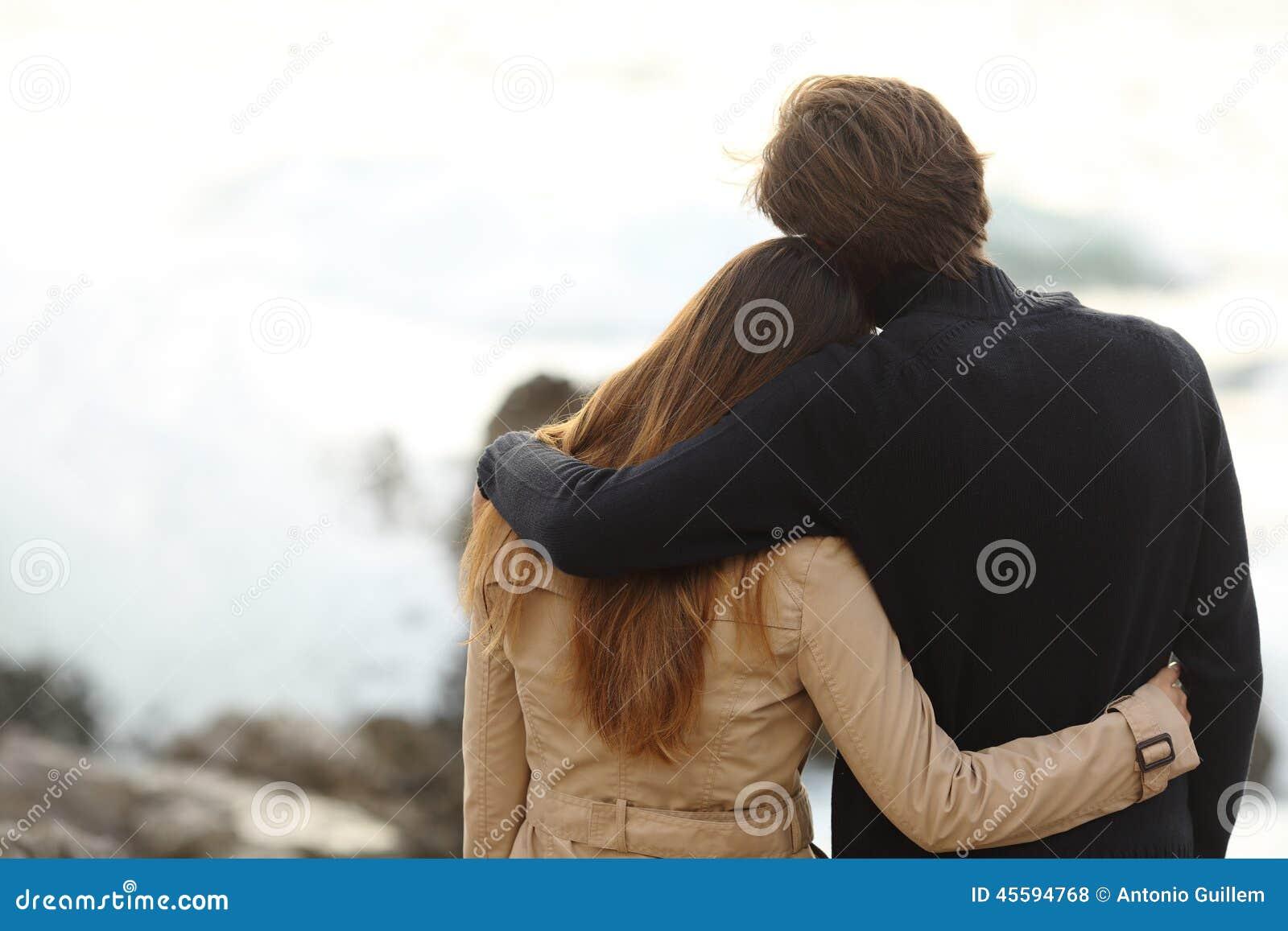 拥抱在冬天的夫妇的后面看法