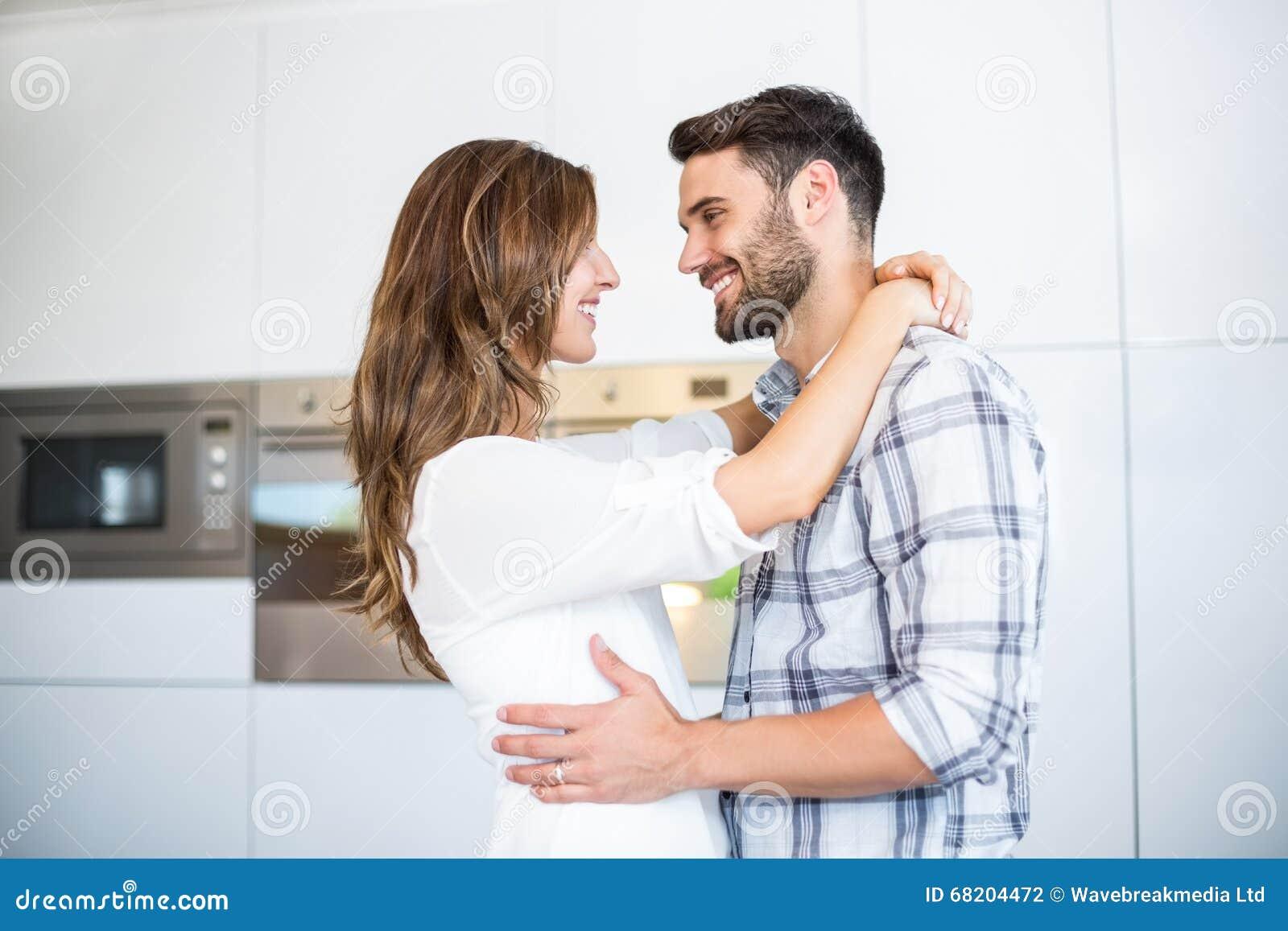 在家拥抱在厨房里的愉快的年轻夫妇.图片