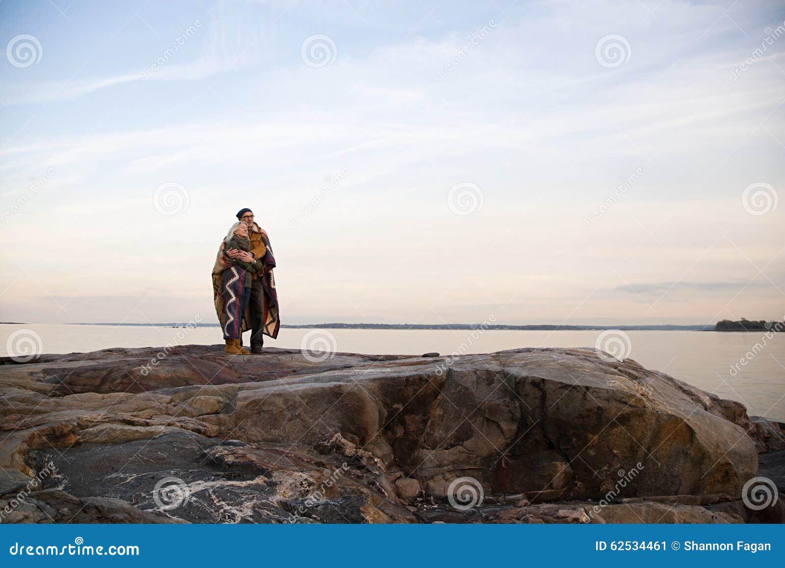 拥抱在岩石的成熟夫妇