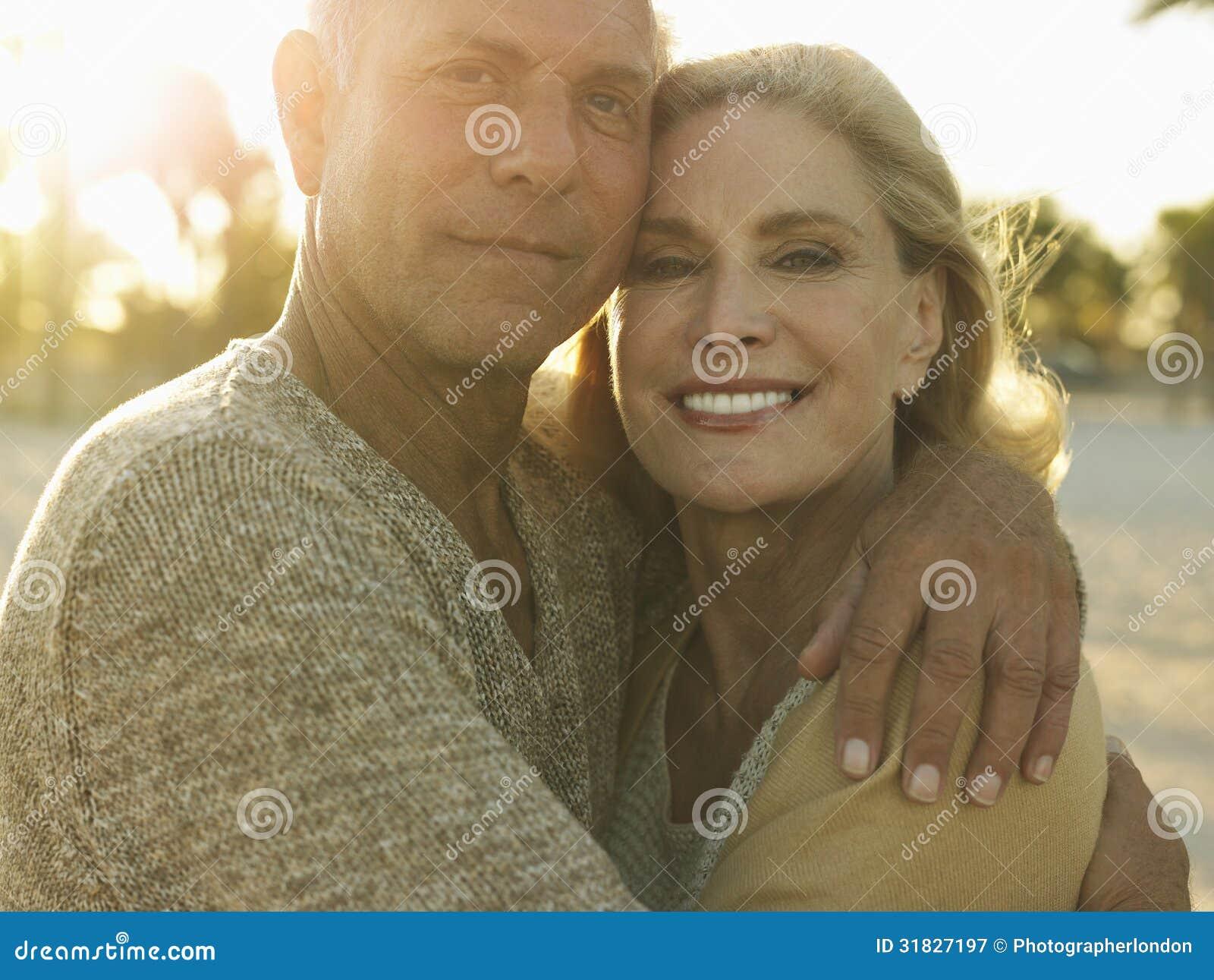 拥抱在海滩的愉快的资深夫妇
