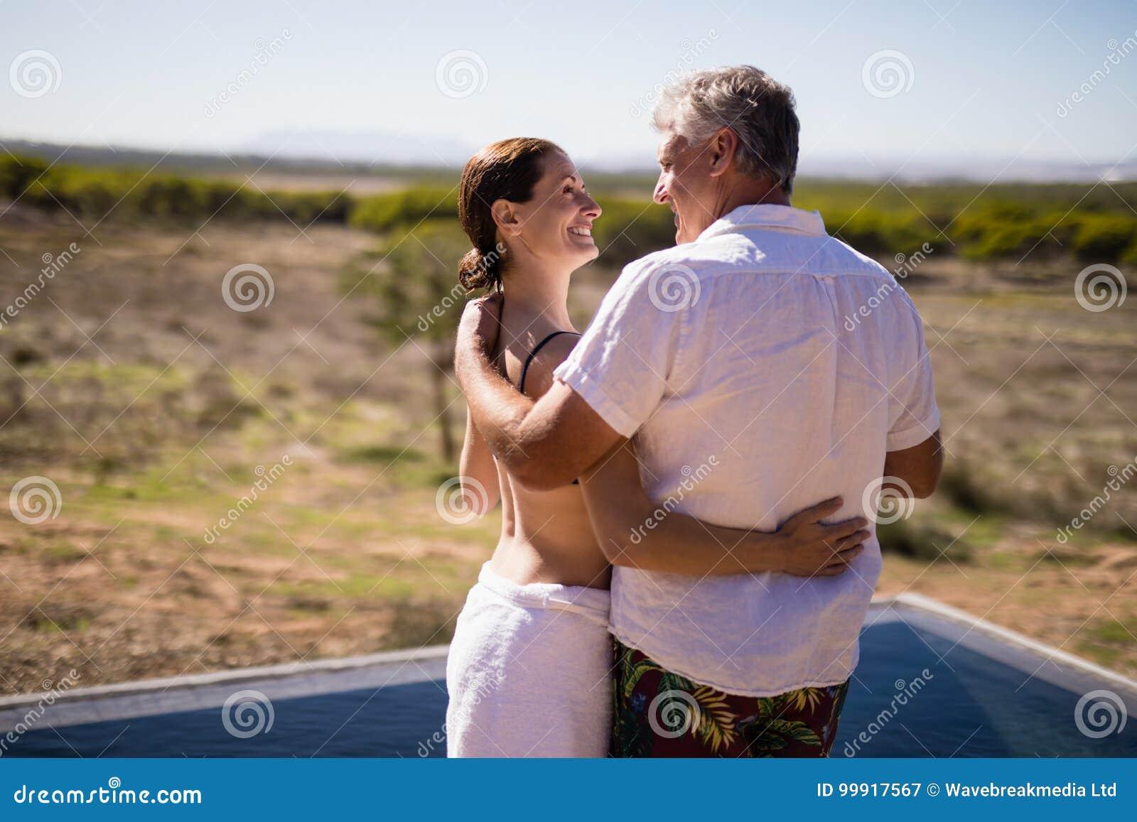 拥抱在游泳池边附近的微笑的夫妇