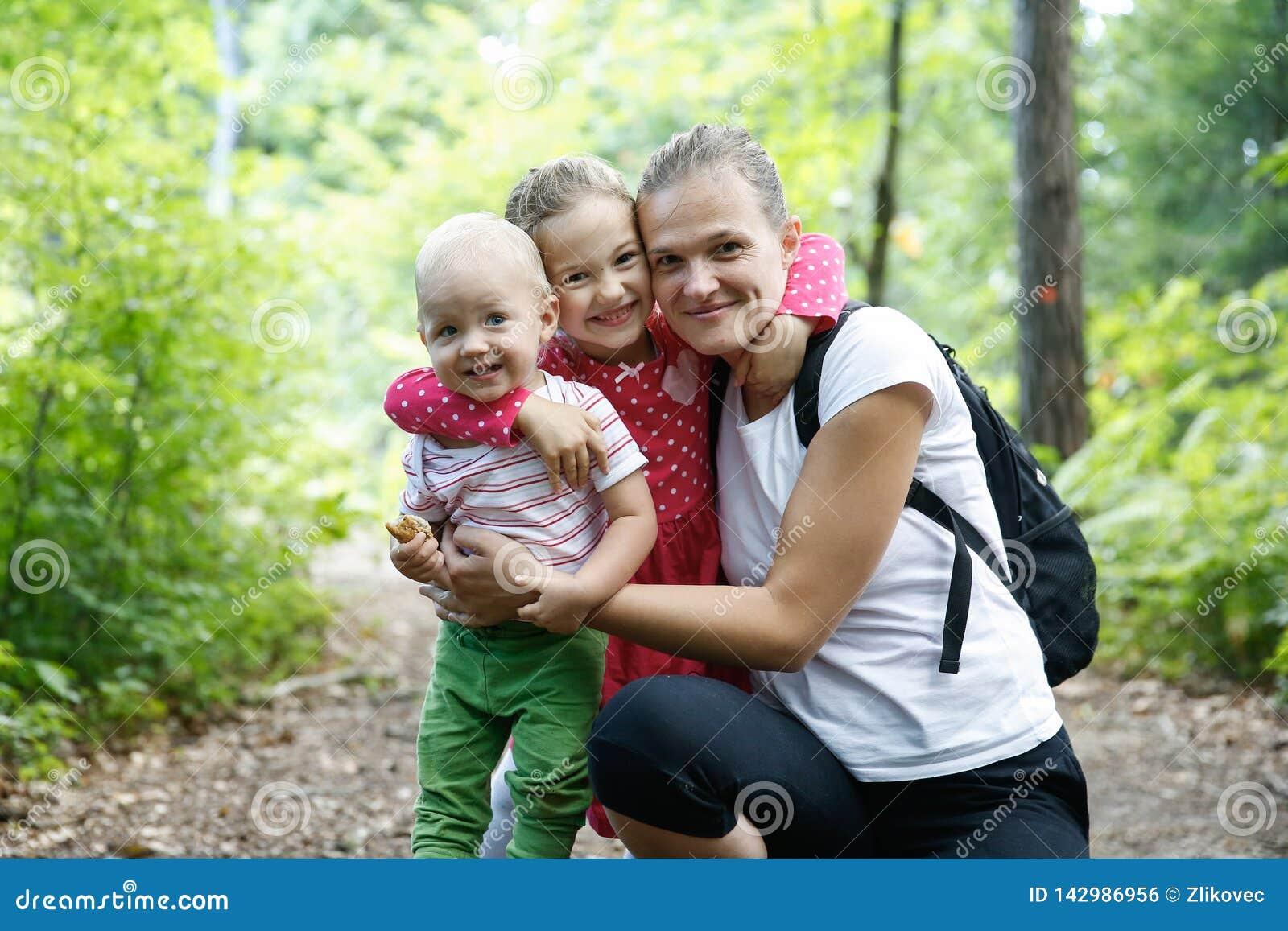 拥抱她的儿子和女儿的致力的母亲,享用室外