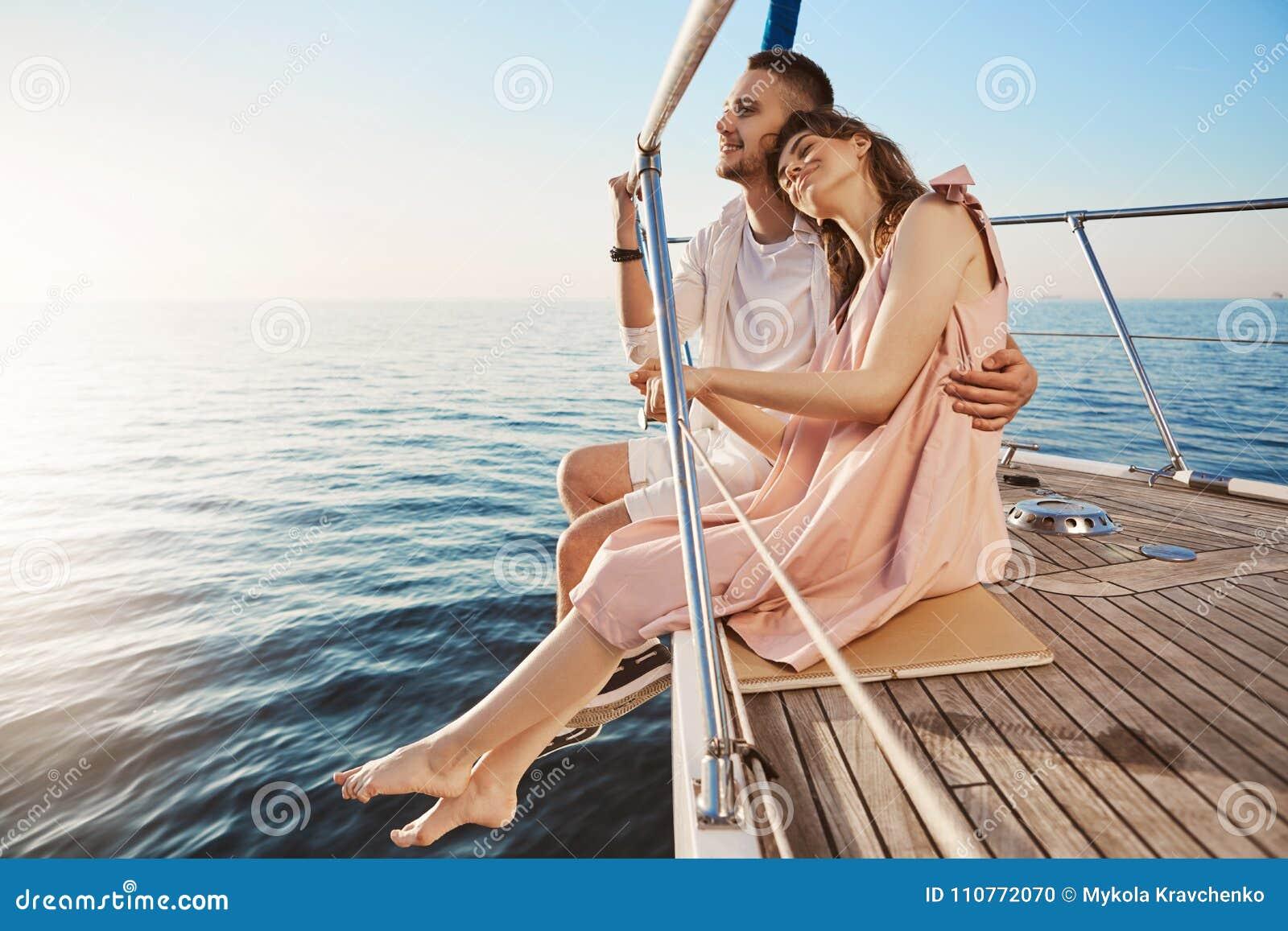 拥抱愉快的美好的成人的夫妇坐游艇的边,观看在海边和,当在度假时 Tan也许退色