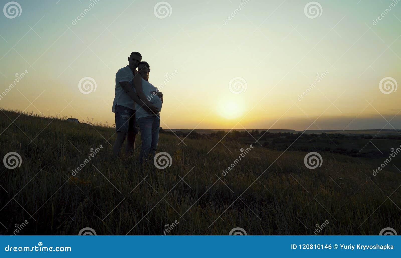 拥抱本质上的浪漫年轻愉快的怀孕的夫妇在日落