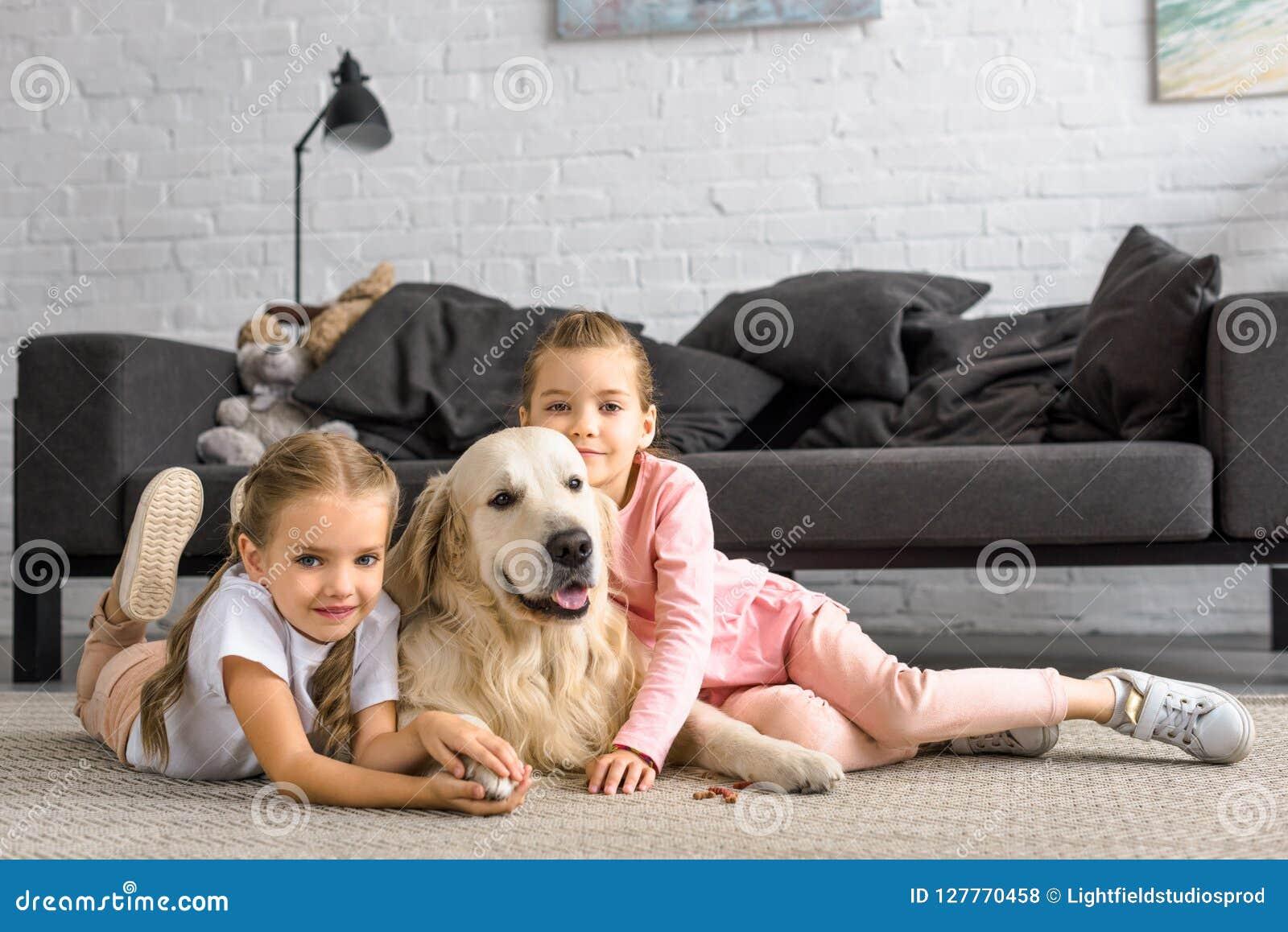 拥抱金毛猎犬狗的可爱的孩子,当坐地板时