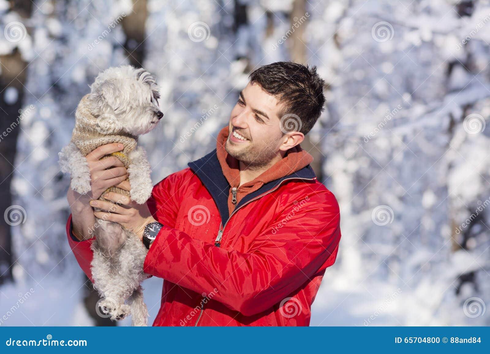 拥抱他的小白色狗的英俊的年轻人在冬天 下雪