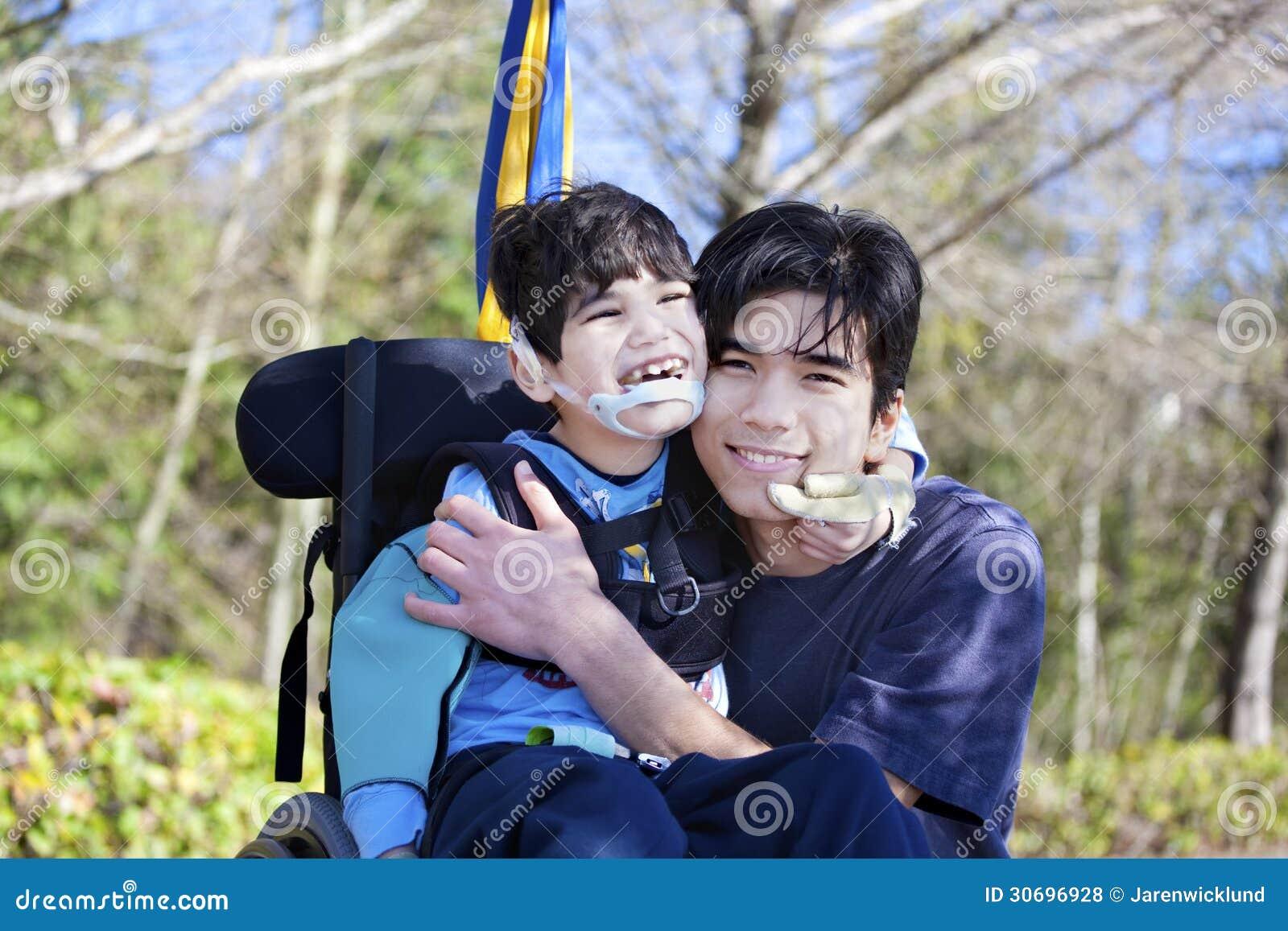 拥抱更老的兄弟的轮椅的小残疾男孩户外
