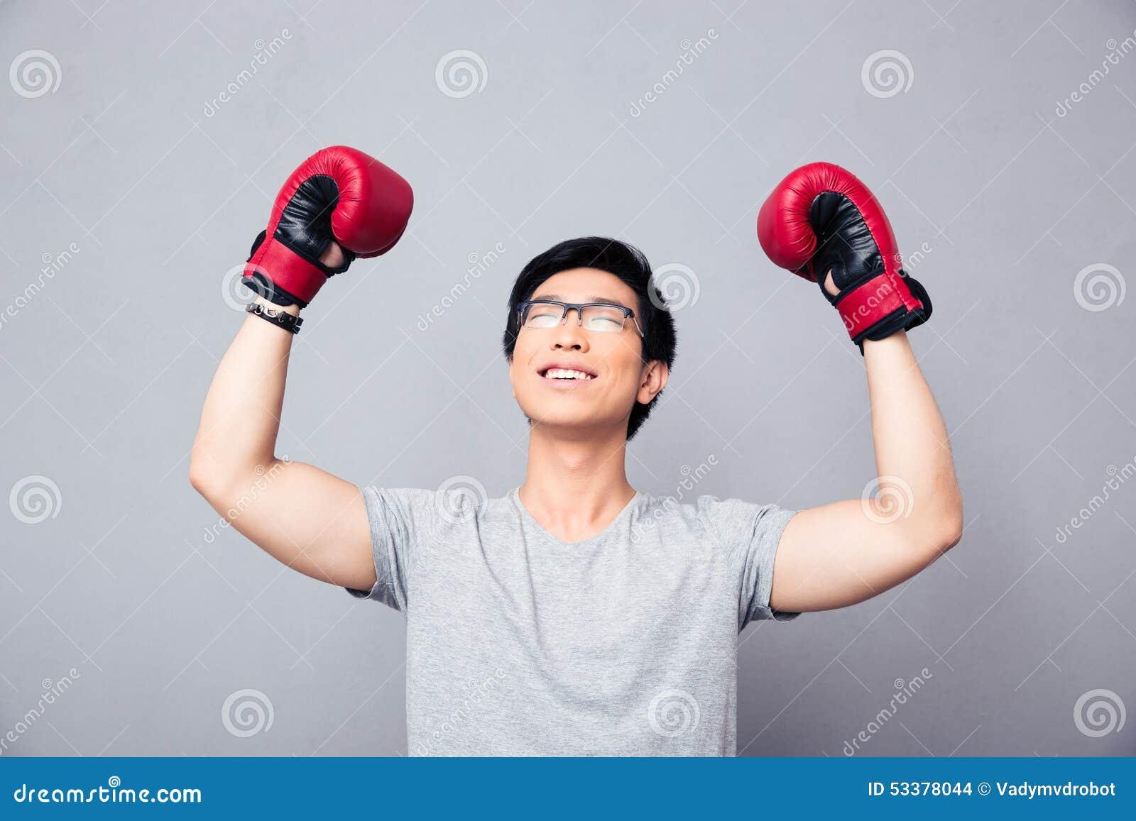 拳击手套的亚裔人高兴胜利