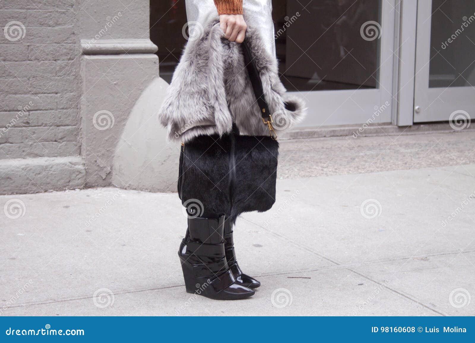 拿着一个毛茸的黑钱包和佩带黑赃物的妇女