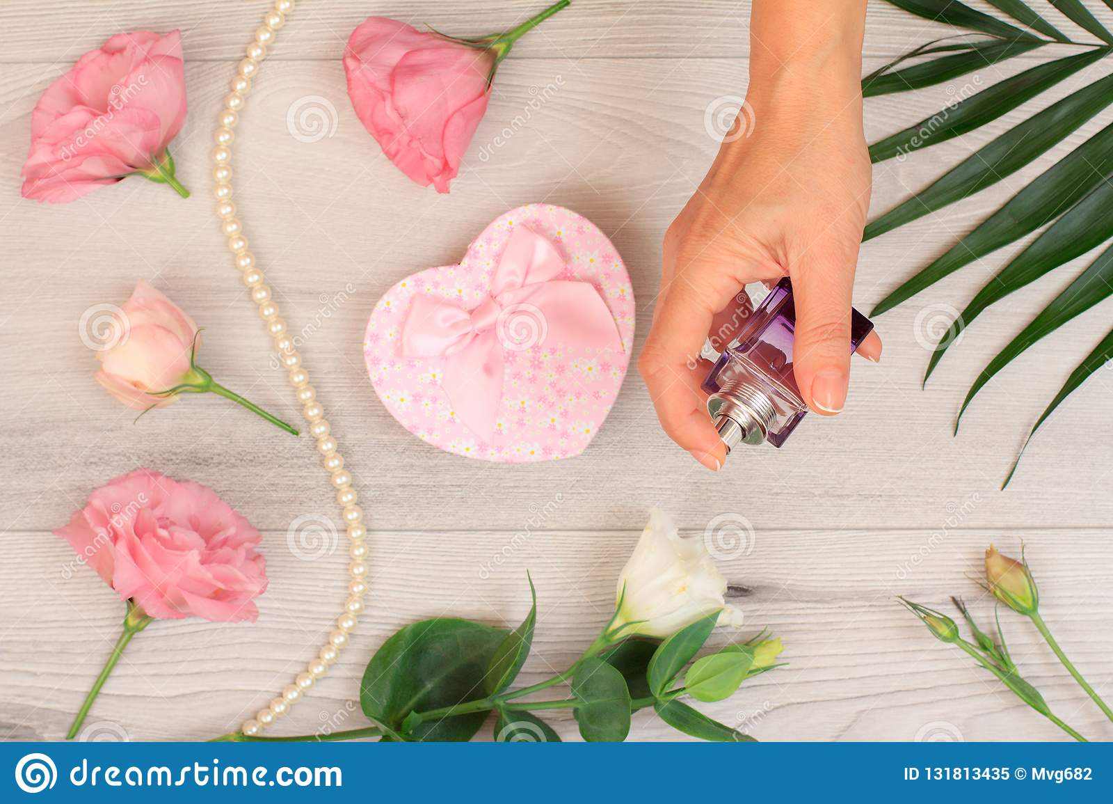 拿着一个瓶香水的妇女在手上有在背景的花的