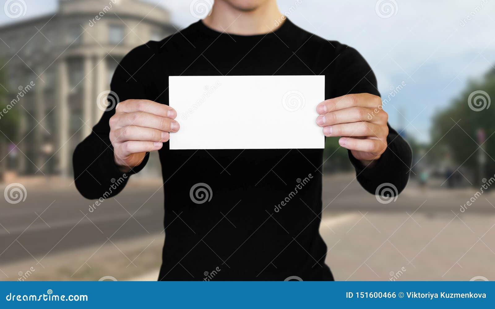拿着一张白色纸片的一个人 拿着小册子 ?? 城市的背景