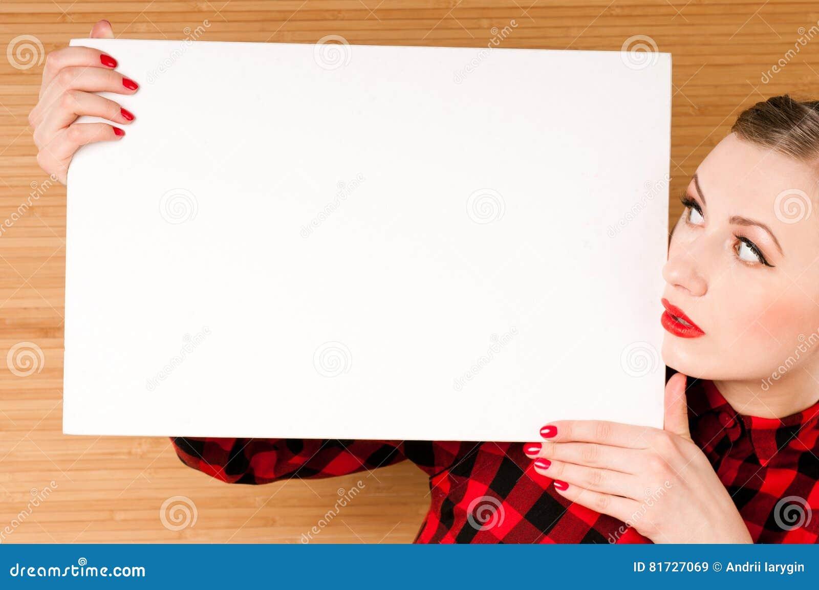 拿着一张空的白色海报的美丽的女孩