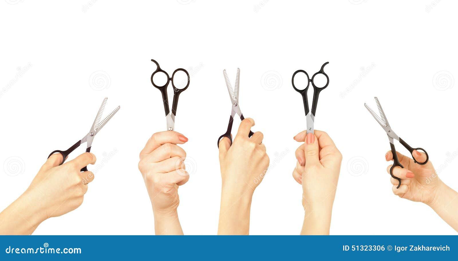 拿着一把剪刀剪的头发的手在白色.图片