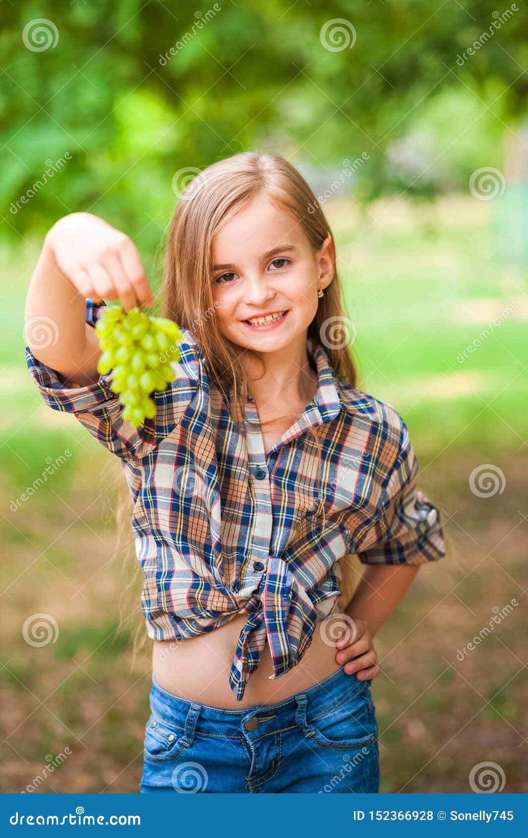 拿着一束绿色葡萄特写镜头的格子衬衫和牛仔裤的女孩 收获葡萄和女孩的种植园的概念