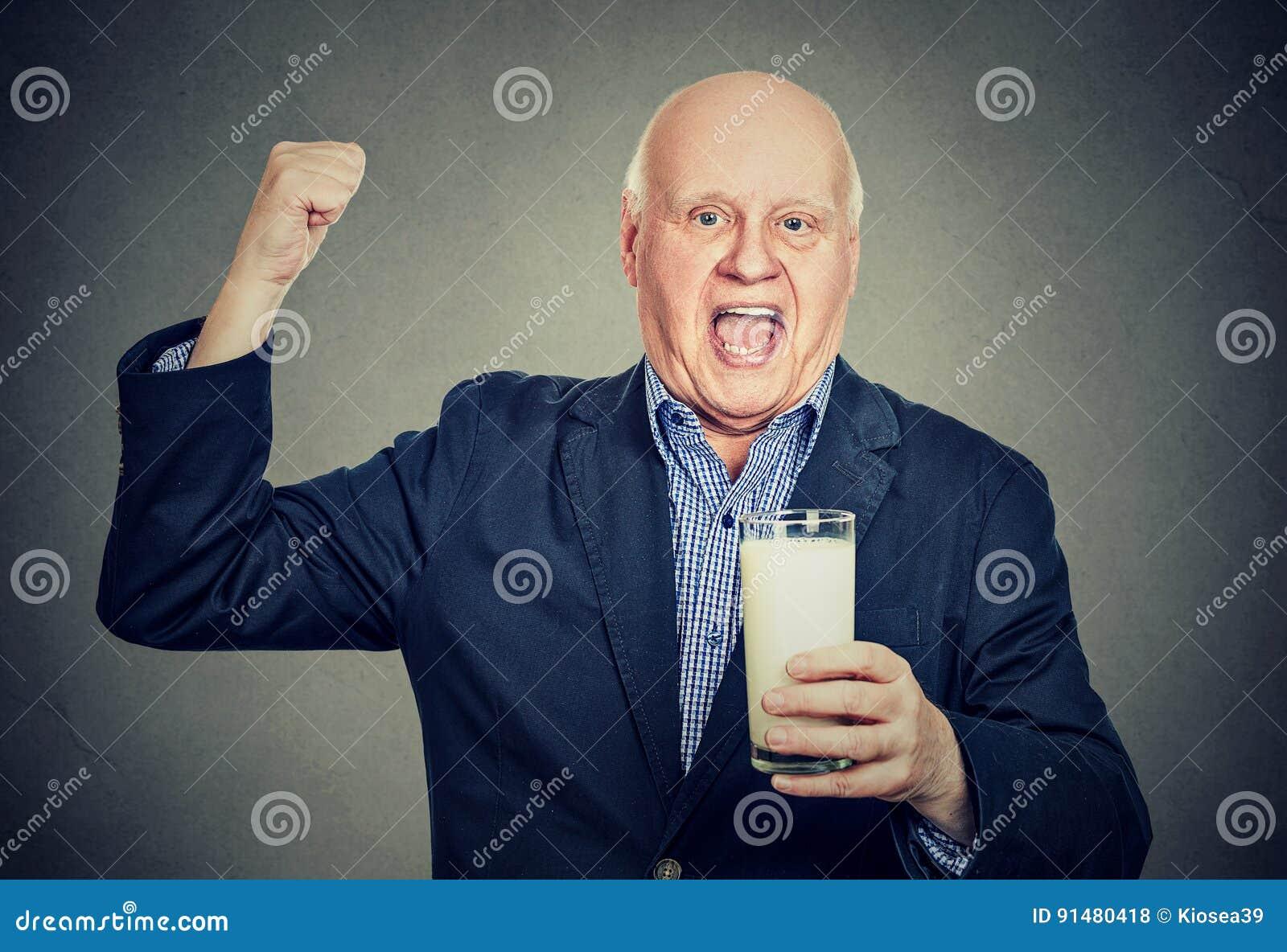 拿着一杯牛奶的激动的资深绅士