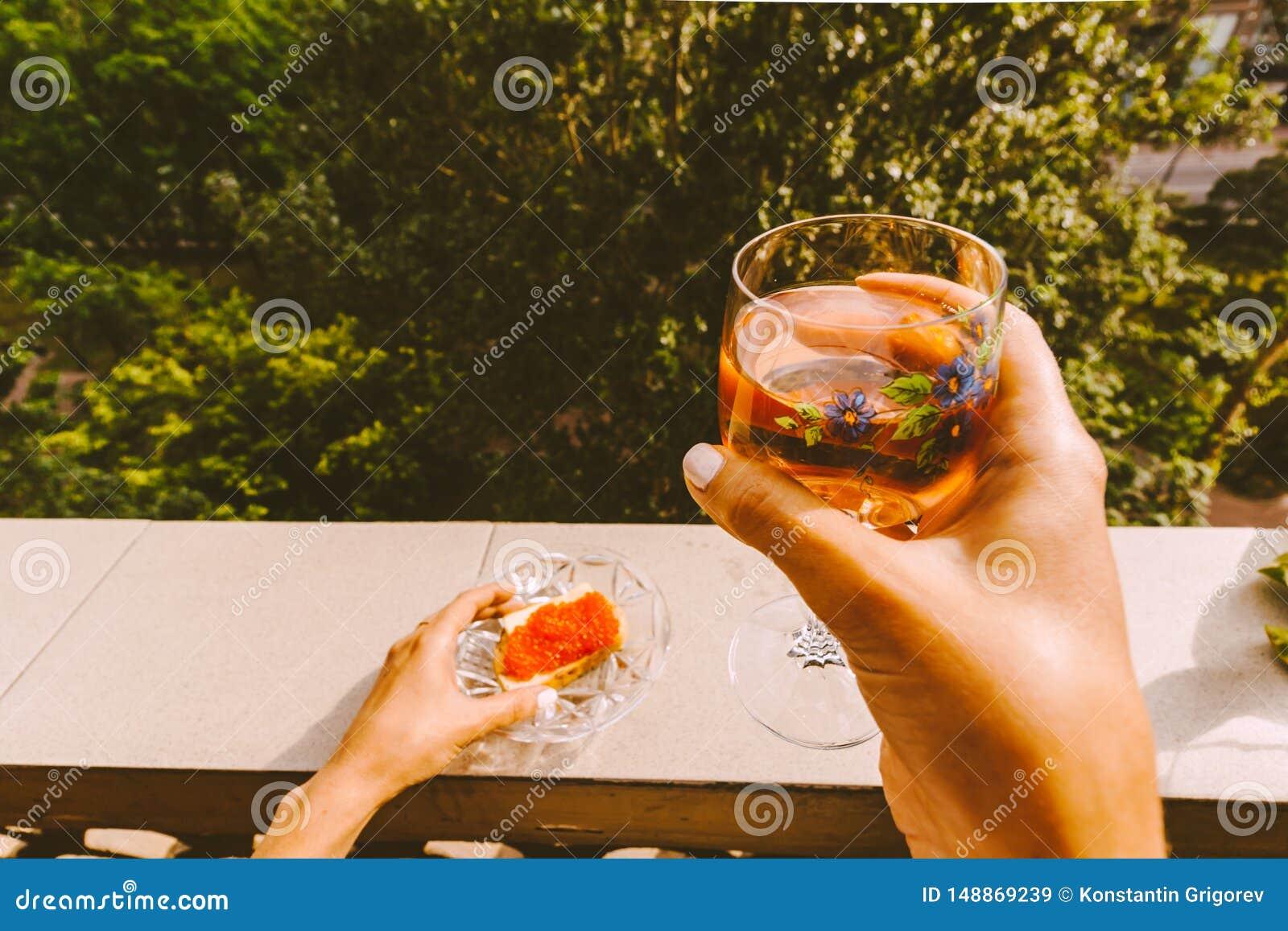 拿着一杯酒的女性手