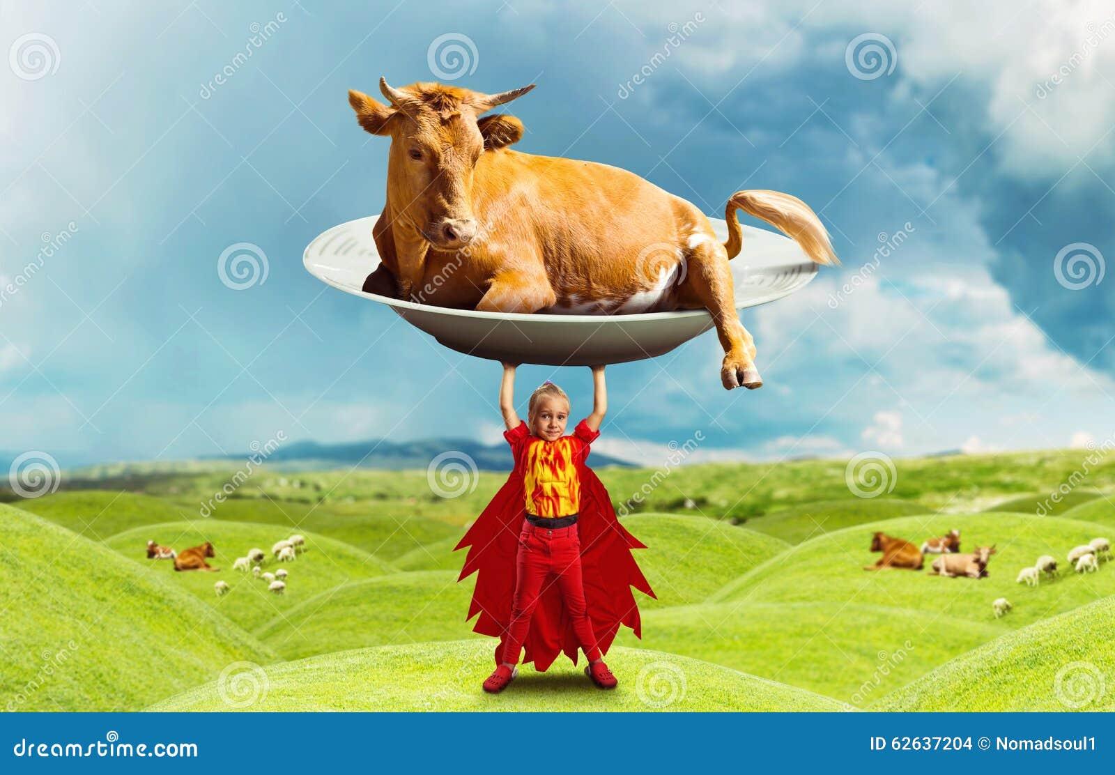 拿着在草甸的服装的小女孩一头大母牛.