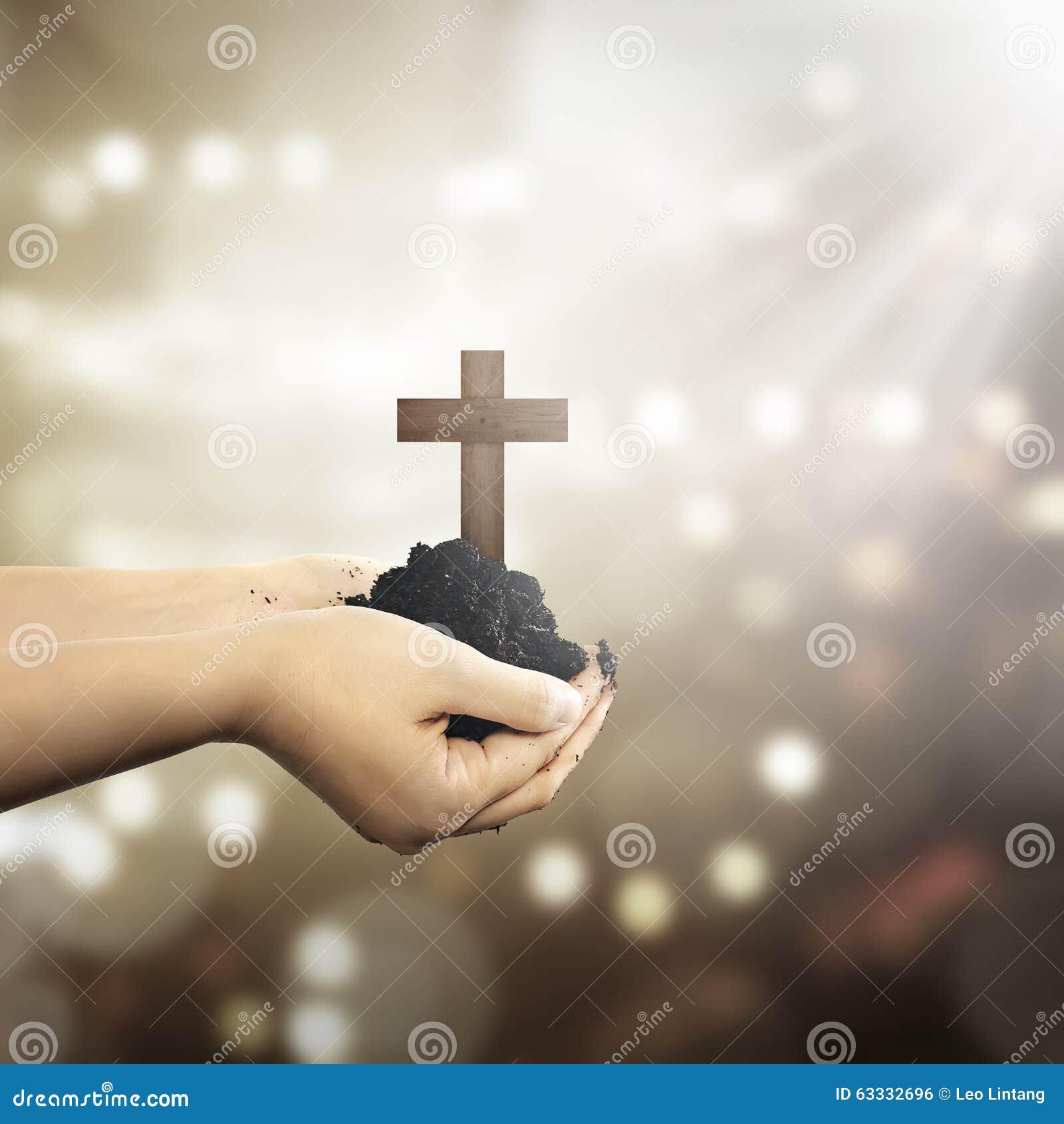 拿着与土壤的人的手基督徒十字架在手上