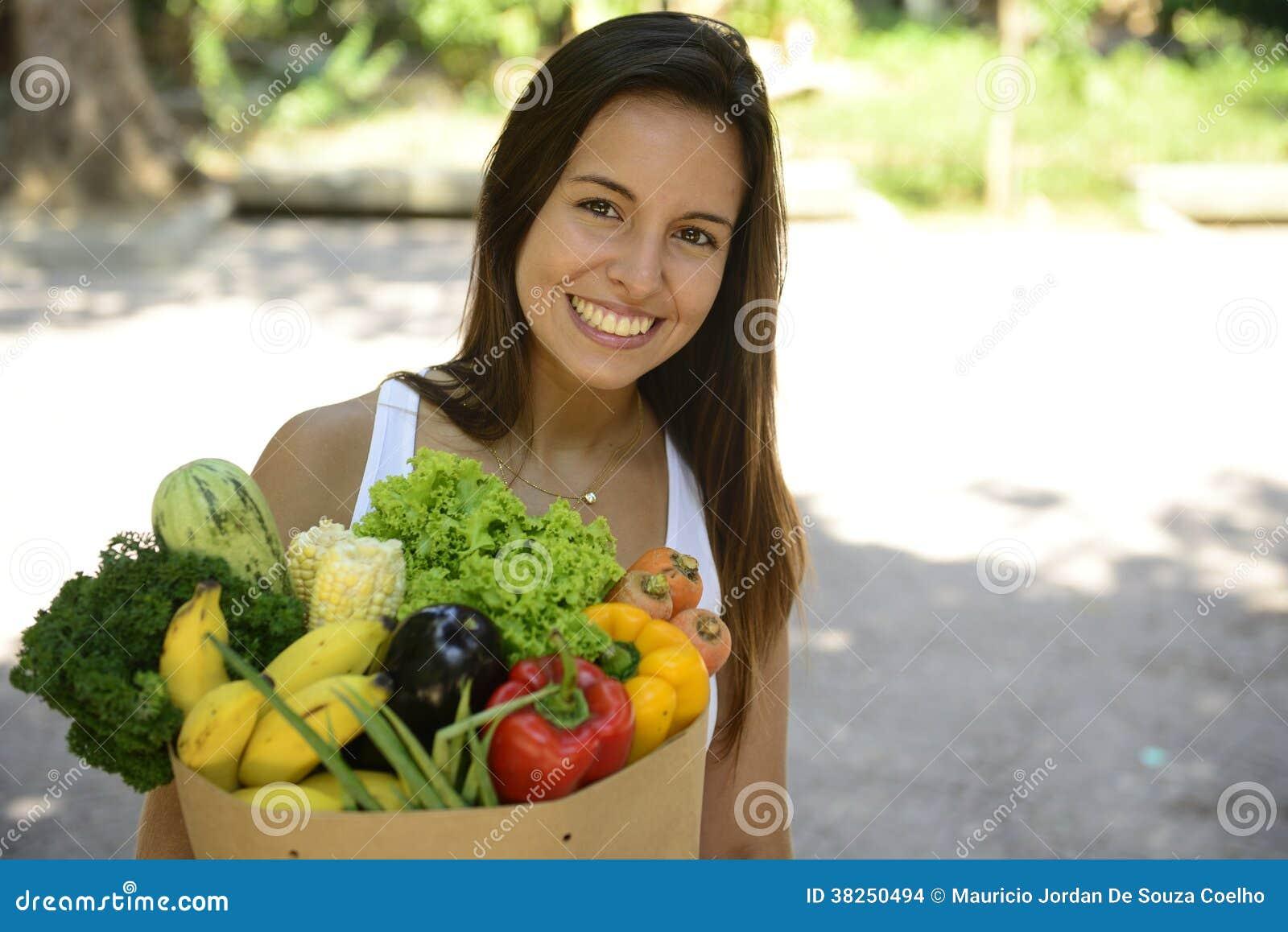 拿着与有机或生物蔬菜和水果的妇女购物的纸袋。