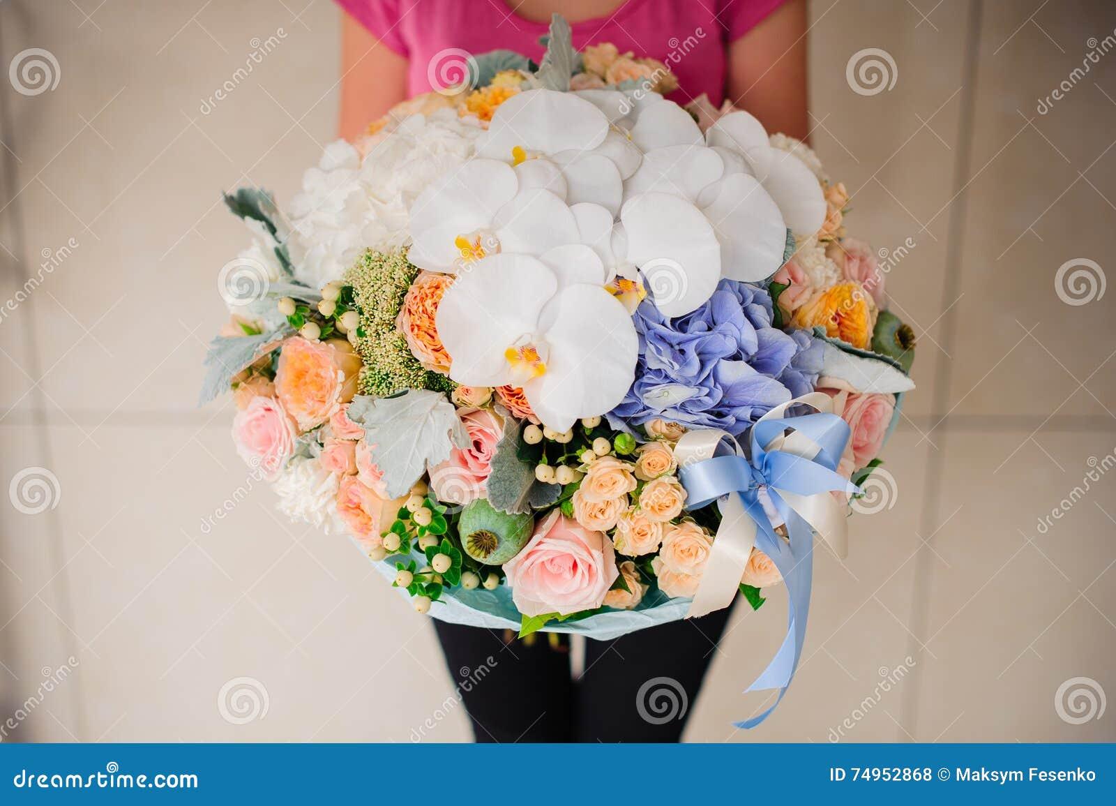 拿着与白色兰花的女孩美丽的混合花花束