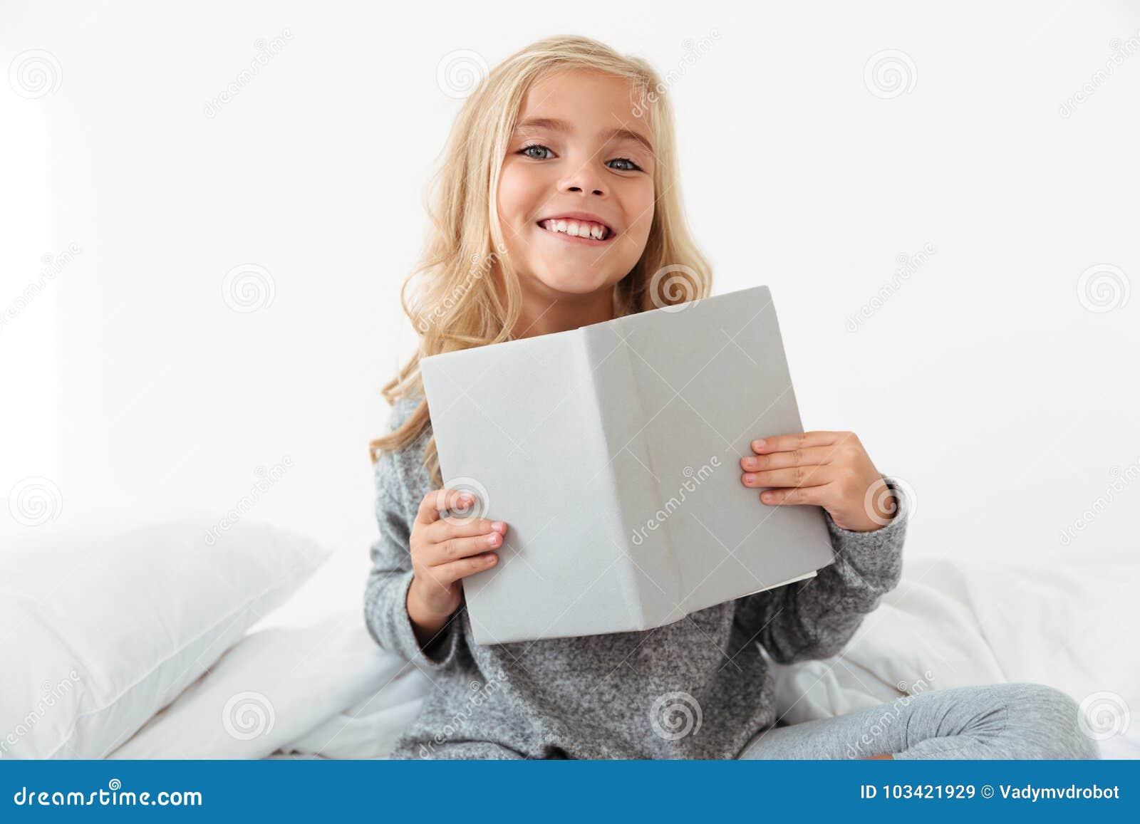 拿着书的灰色睡衣的快乐的小女孩,看加州