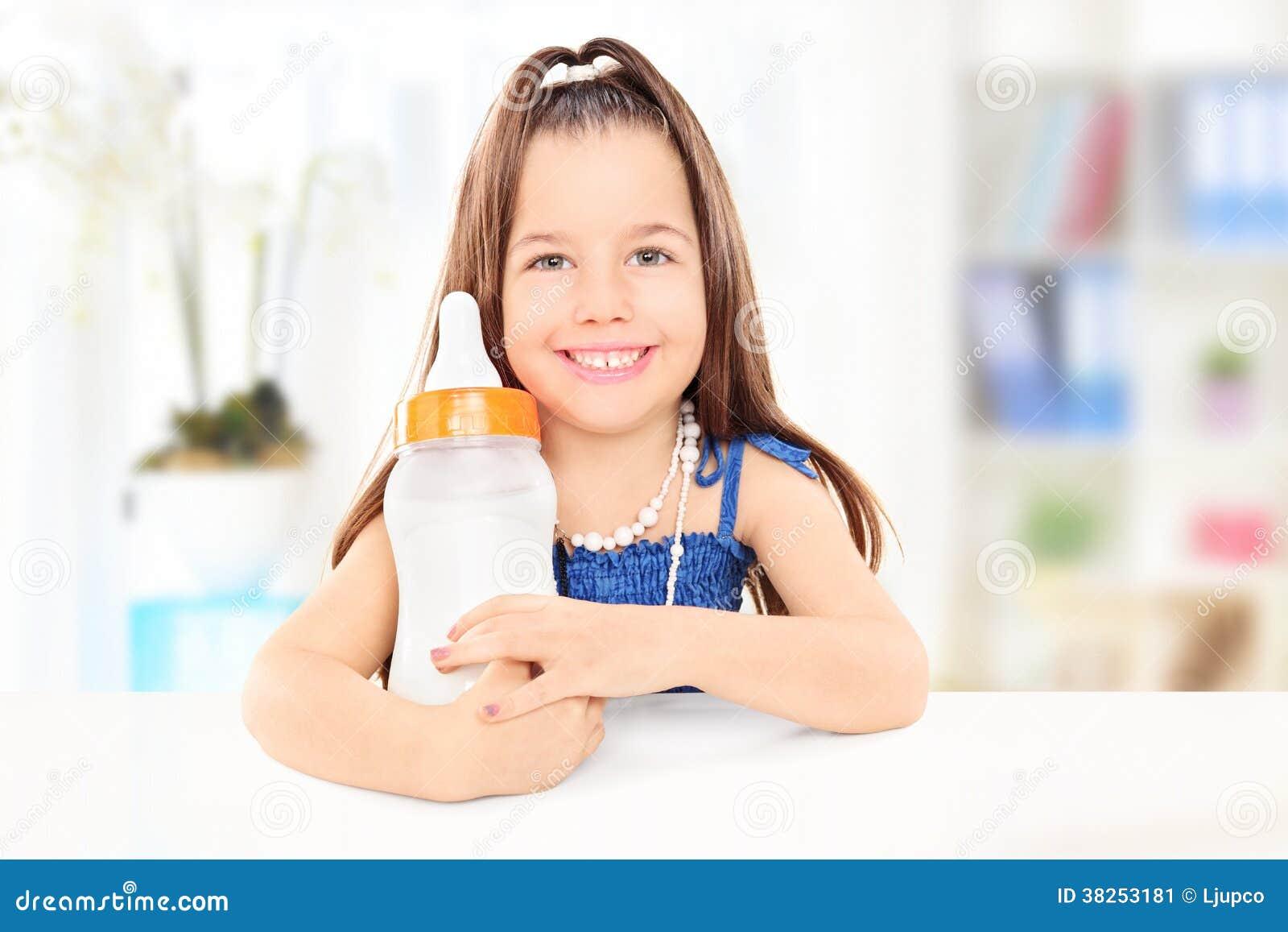 拿着乳瓶的时兴的小女孩有很多牛奶