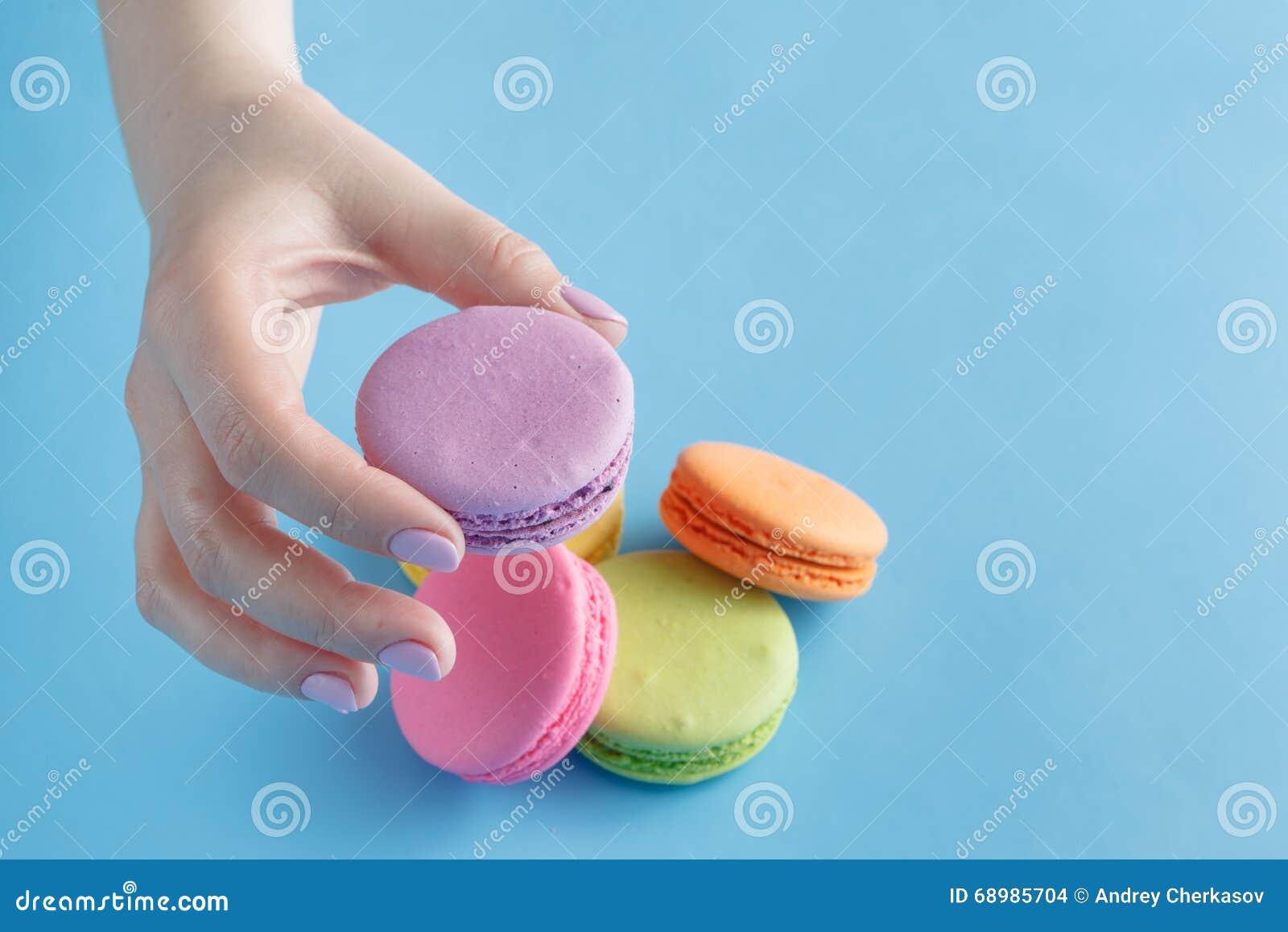 拿着五颜六色的法国蛋白杏仁饼干的女性手