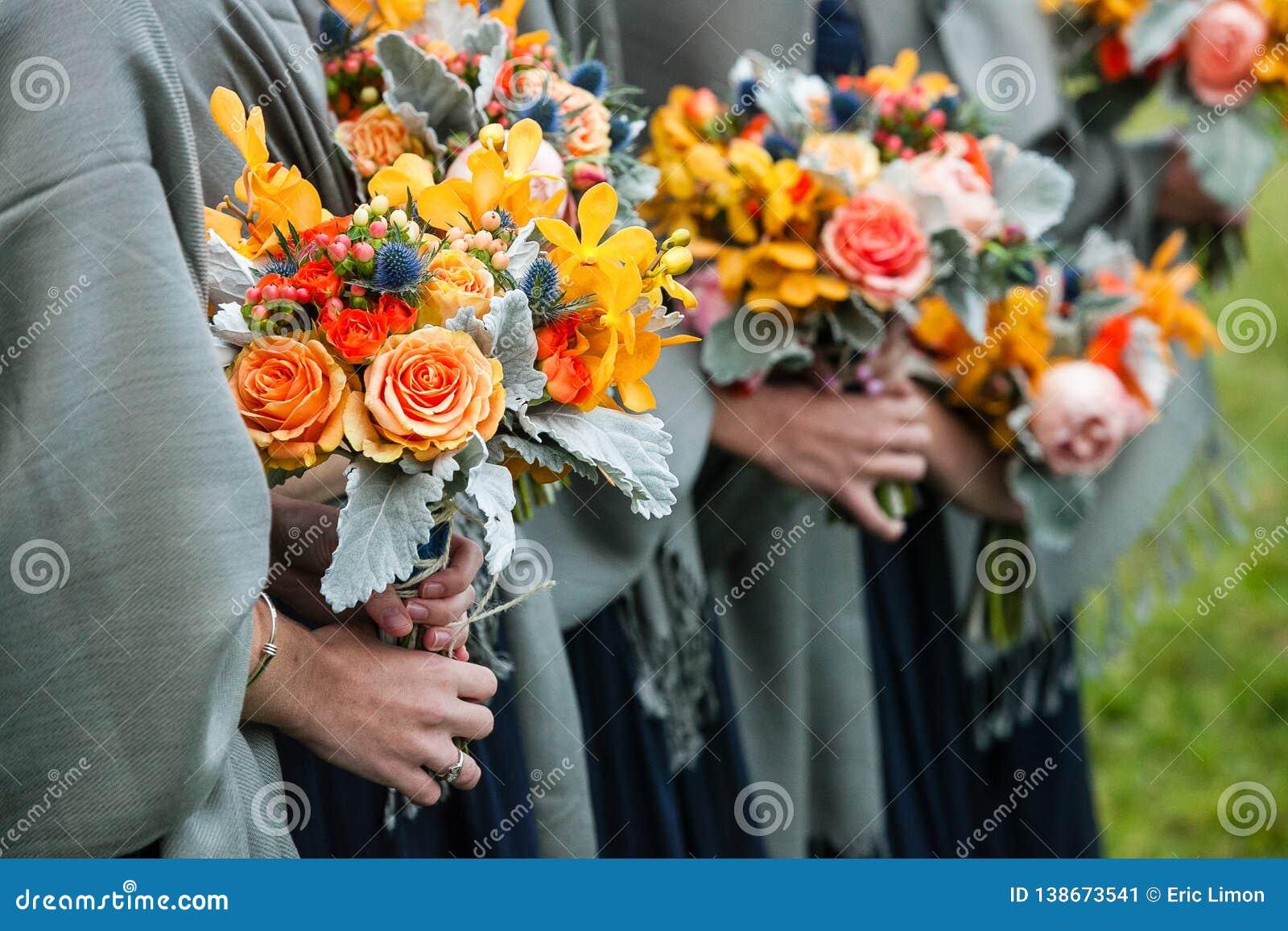 拿着他们与黄色,红色,蓝色和橙色花的女傧相婚姻的花束