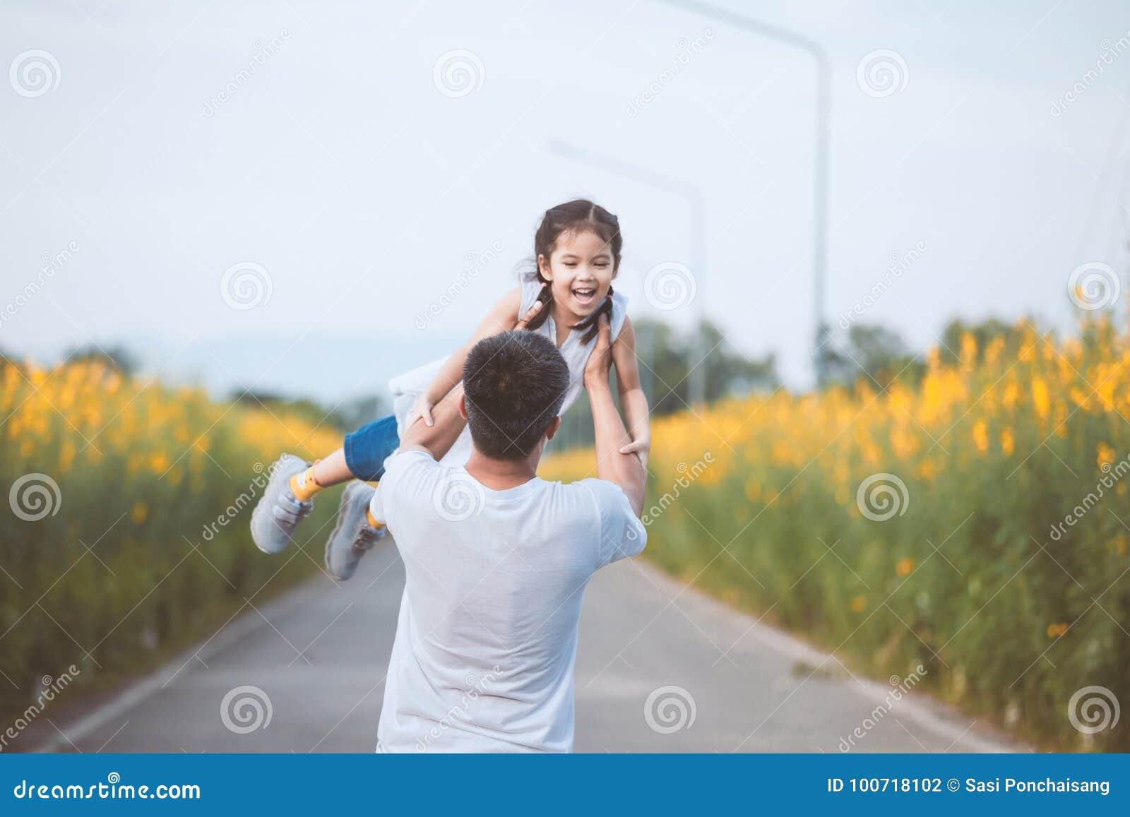 拿着他的孩子的愉快的亚裔父亲转动与乐趣
