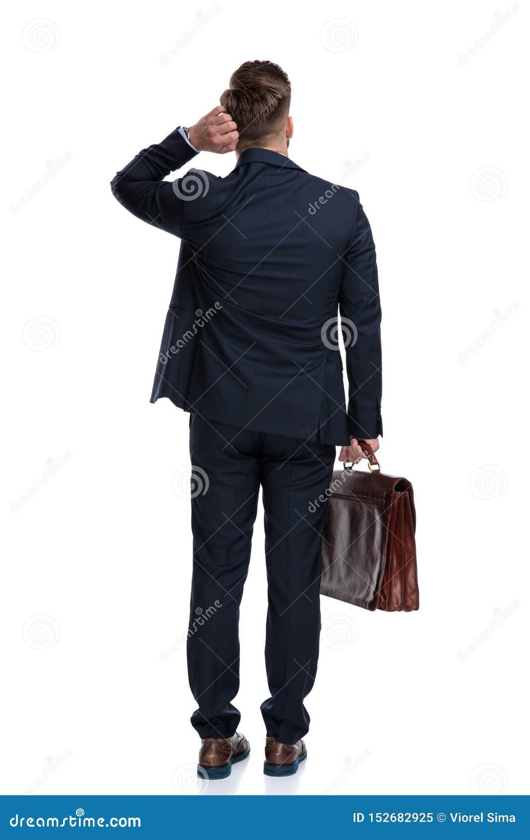 拿着他的手提箱的一个缺乏信心的商人的背面图