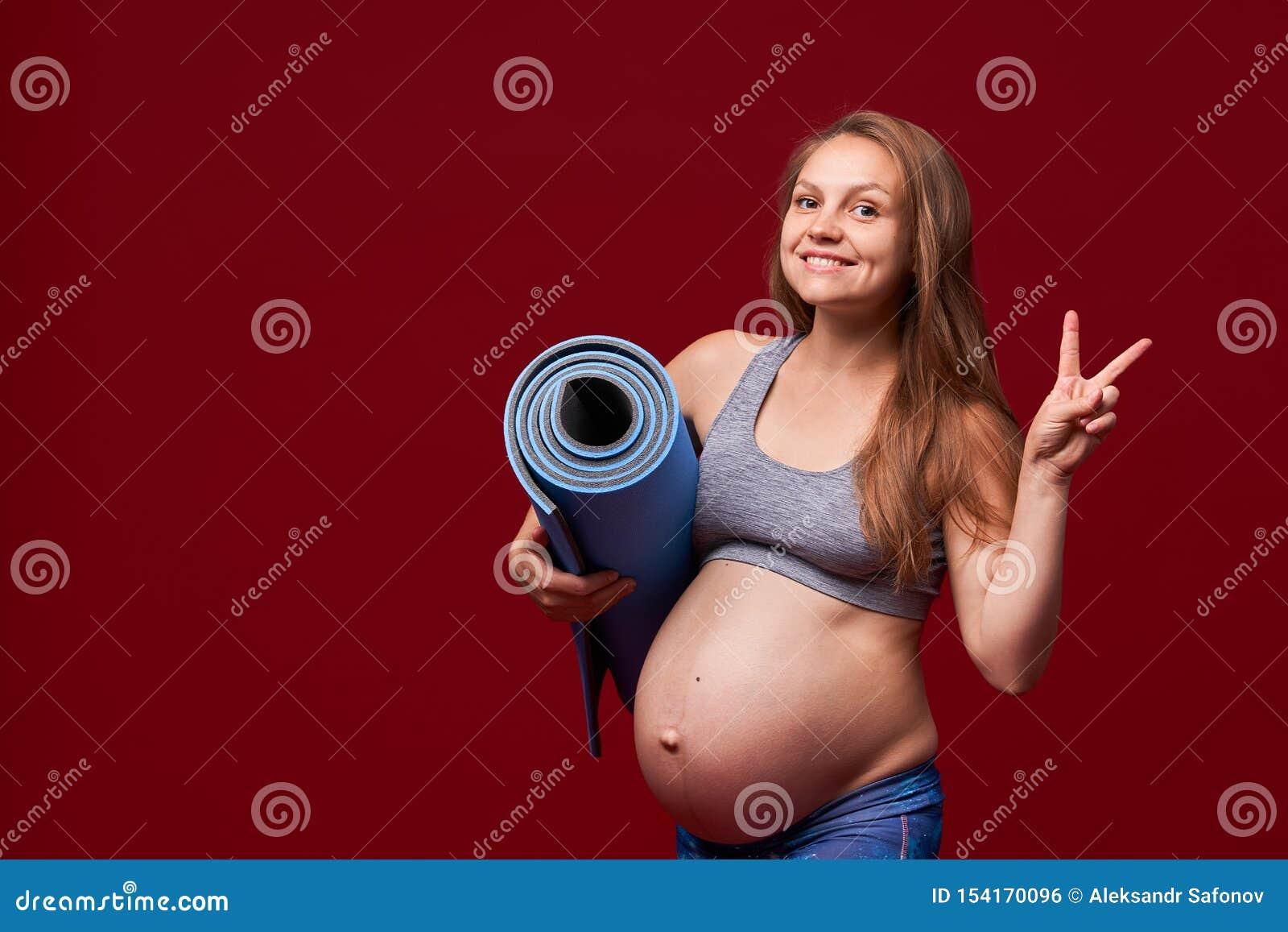 拿着体育席子在她的手上的怀孕的女孩,显示胜利姿态  怀孕体育的衣裳的正面微笑的妇女